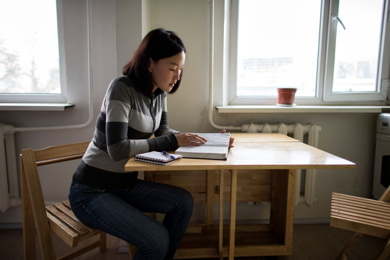 A woman studies the Book of Mormon at her table