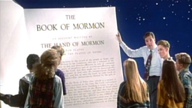 A group of students and their teacher examine a very large copy of the Book of Mormon
