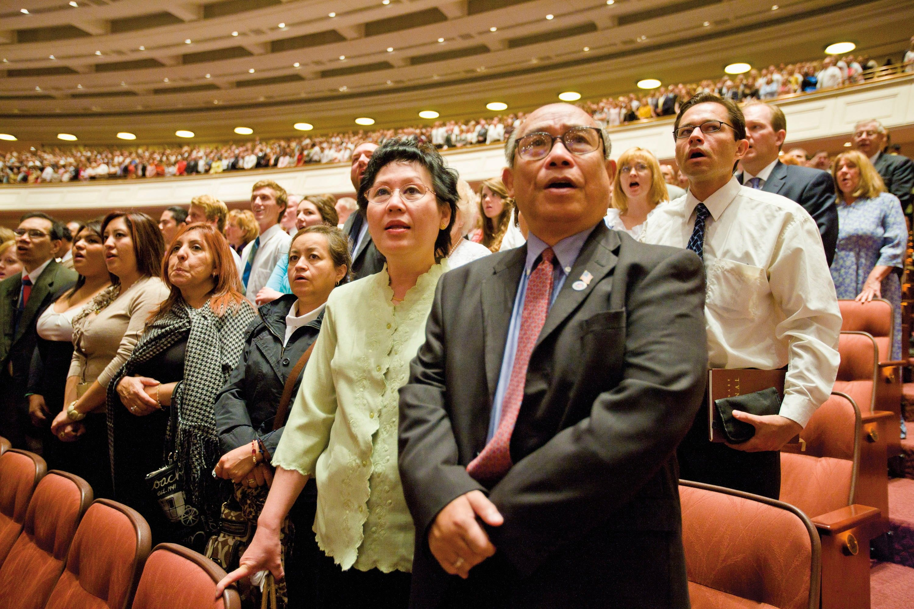 A couple standing and singing with the congregation inside the Conference Center.
