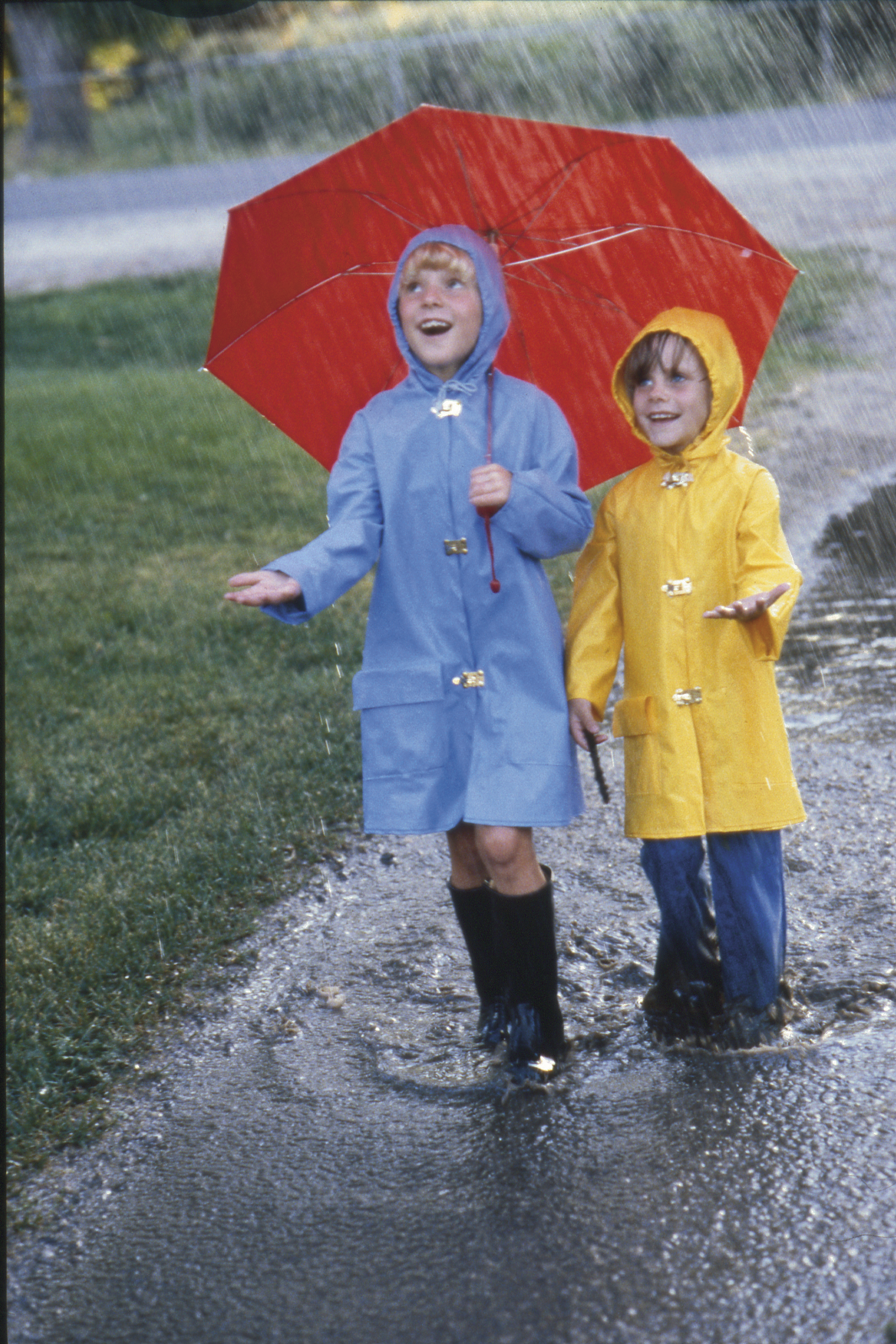 Two girls in raincoats and an umbrella play outside in the rain and puddles.
