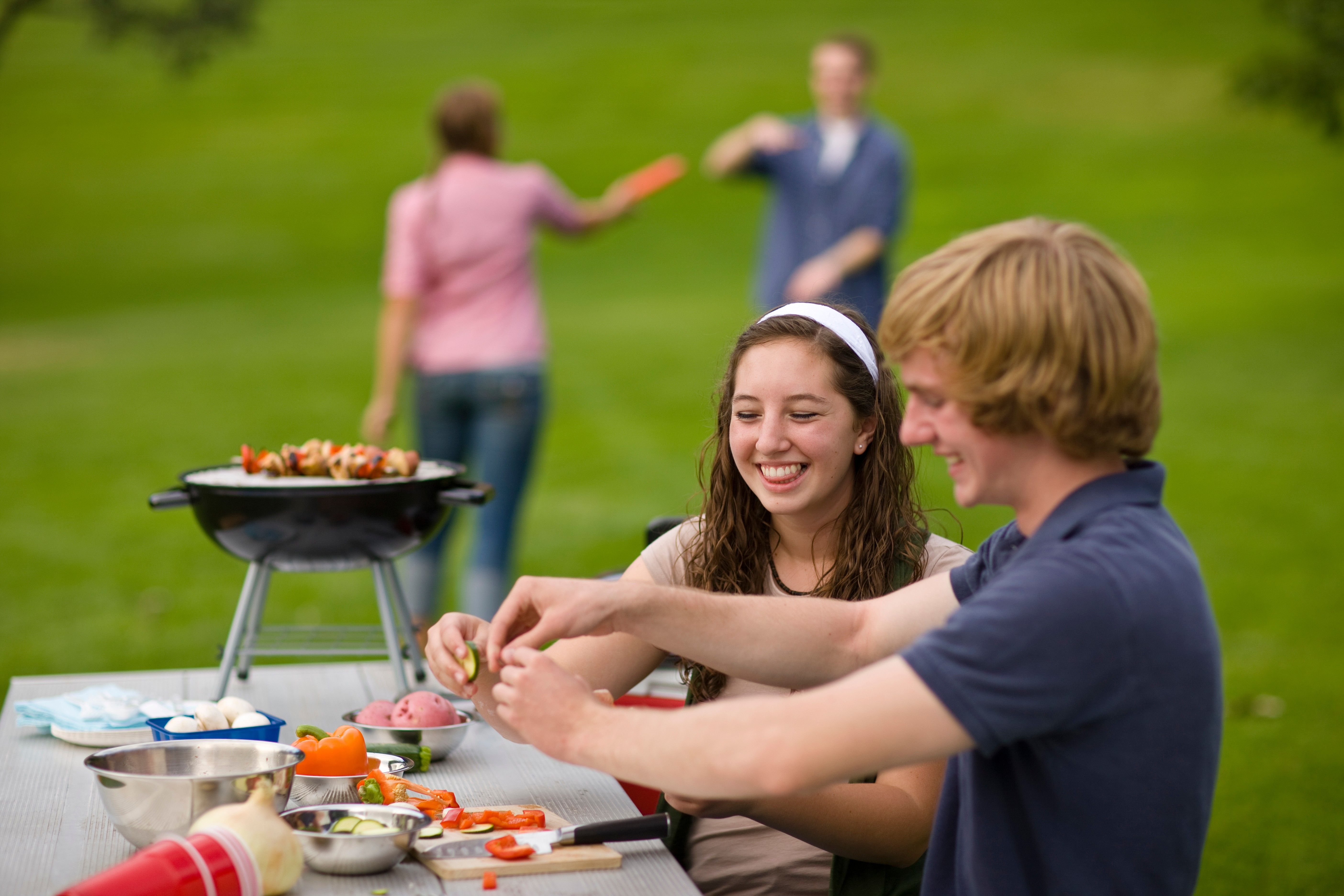 A teenage couple preparing food on a table at the park.