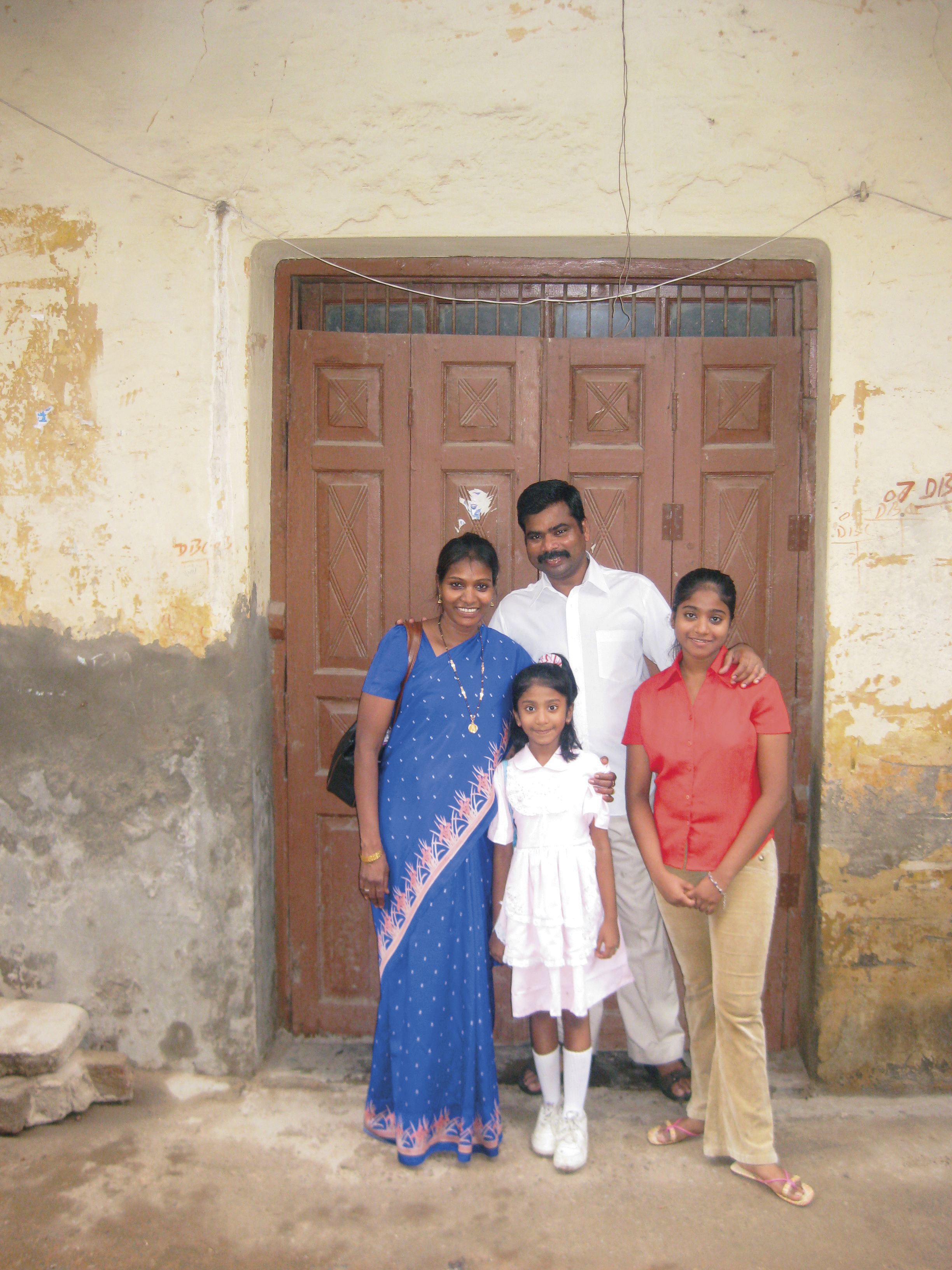 A portrait of a family in New Delhi standing together outside.