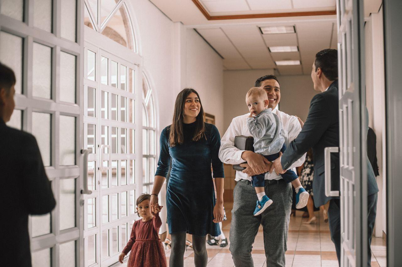 Una familia es recibida al entrar a una capilla