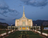 The Ogden Utah Temple in the evening, lit up from without and within, with a green lawn leading up to it.