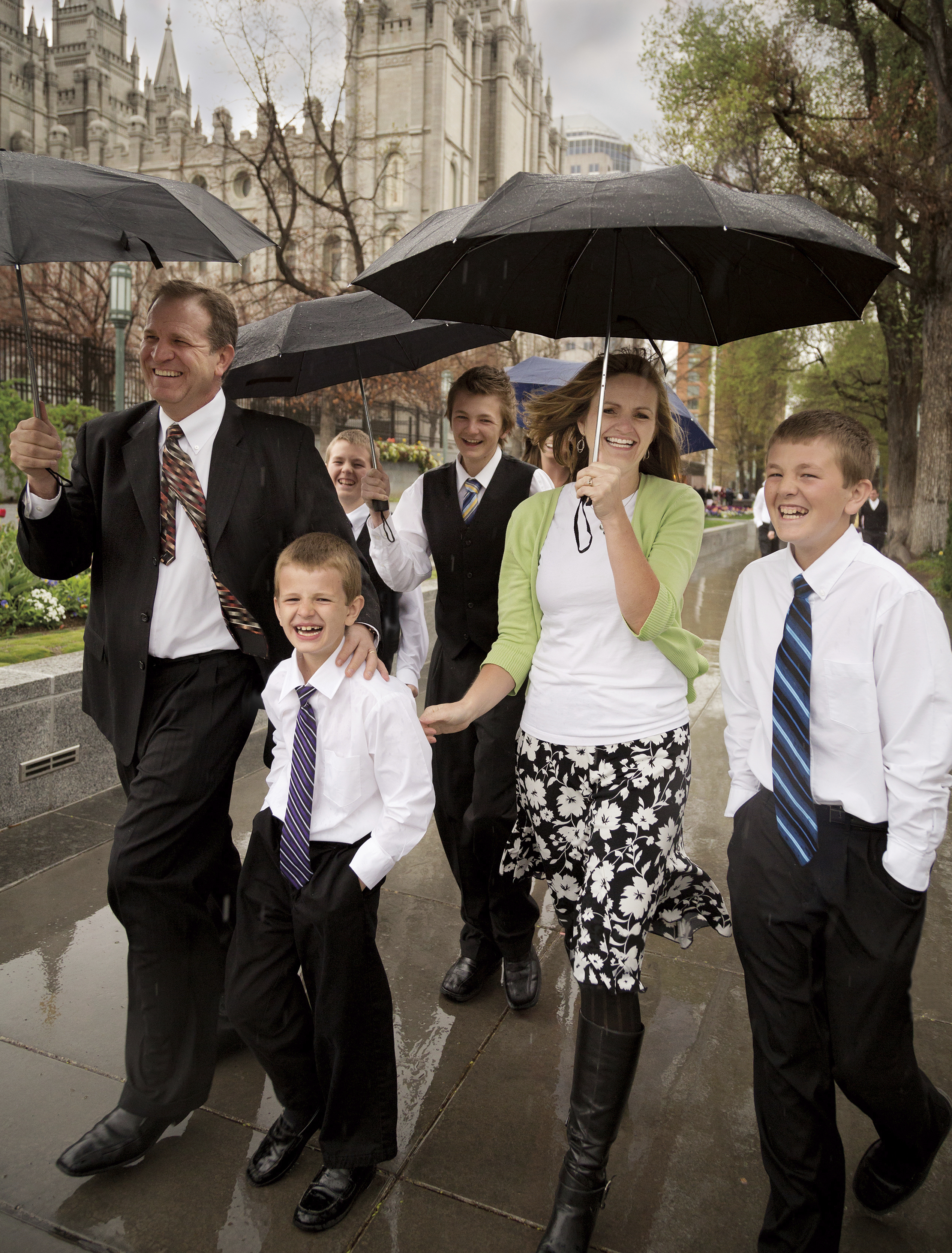 A family holding umbrellas as they walk through rain to the Conference Center.