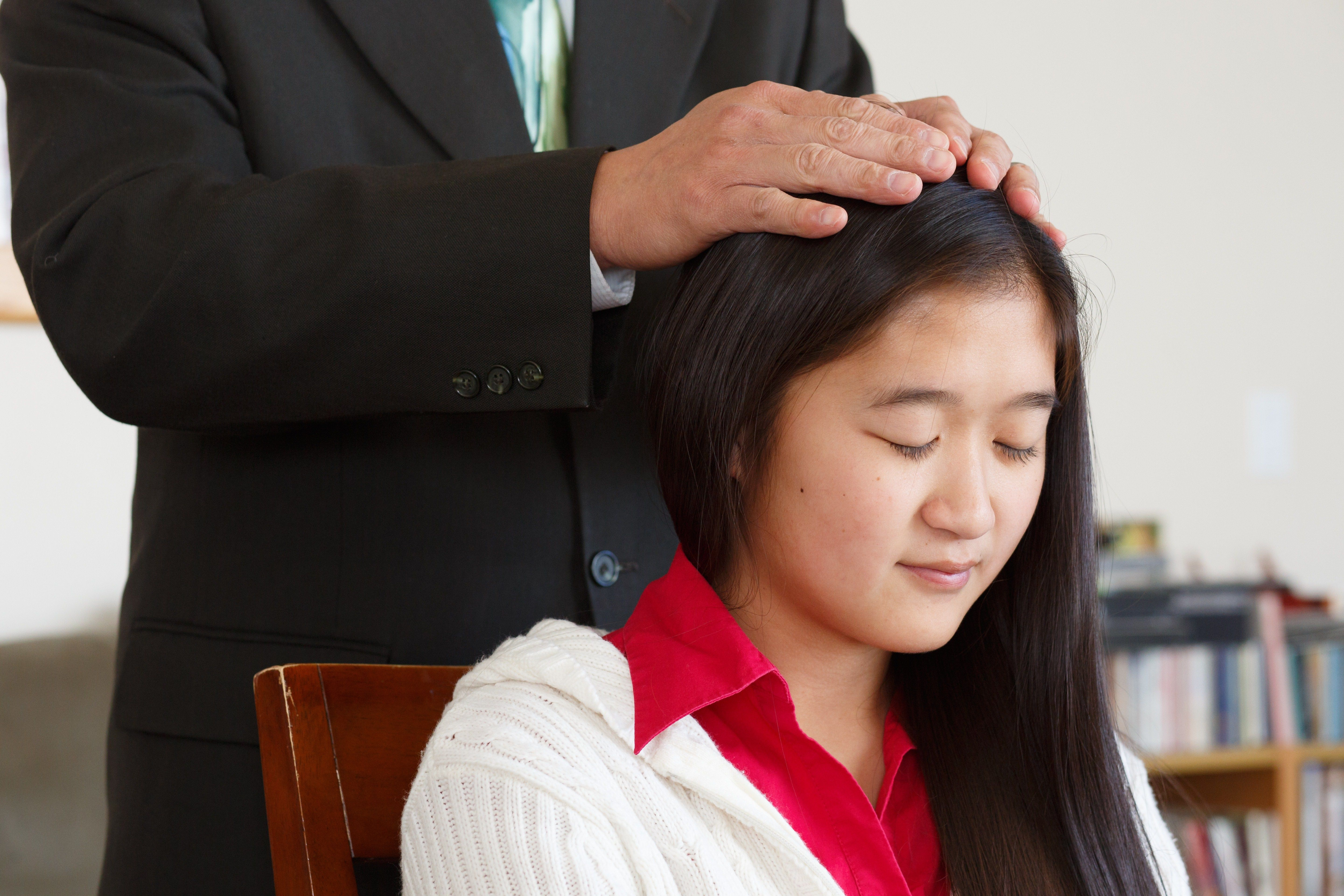 A young woman receiving a priesthood blessing.