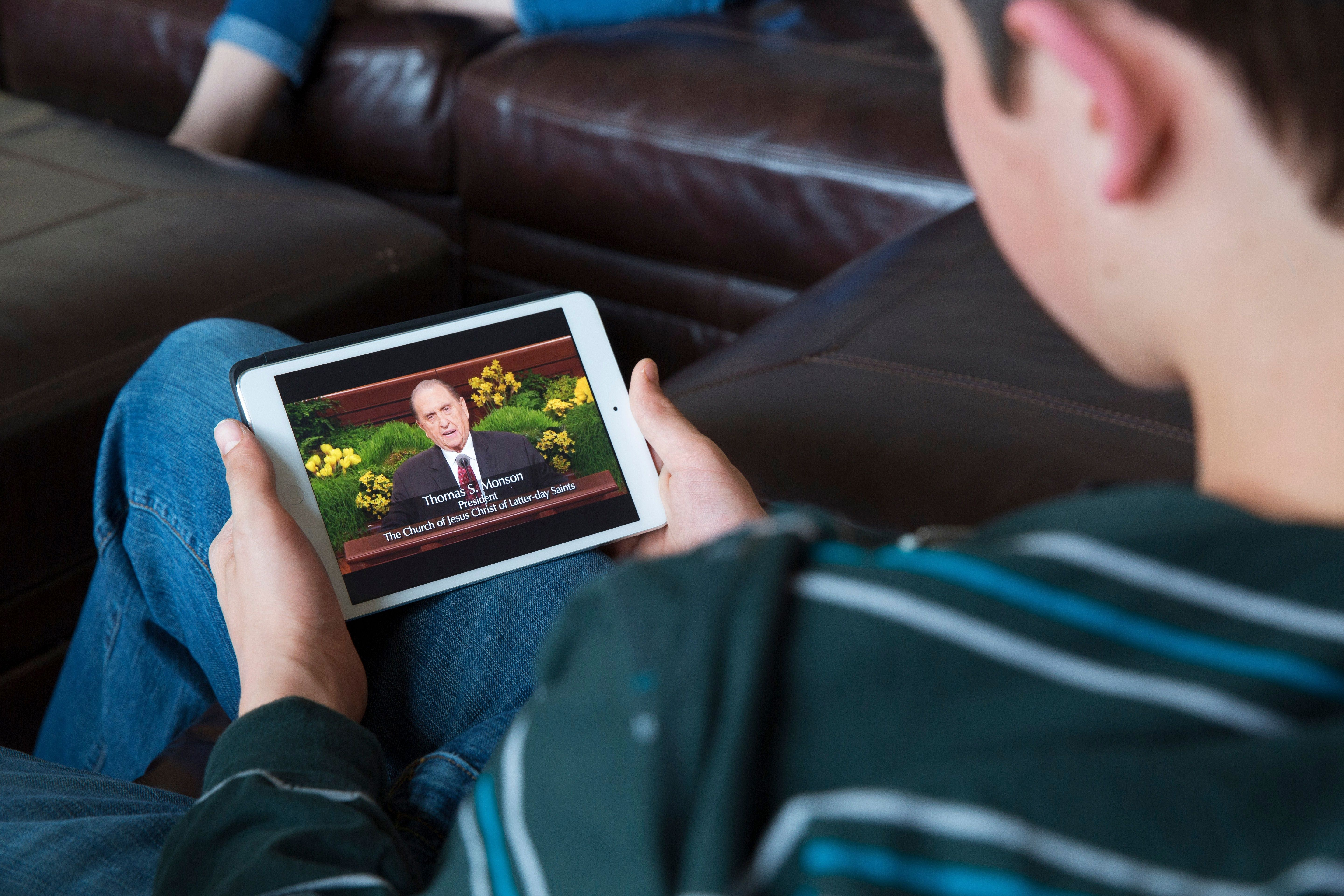 A young man at home watching general conference on his tablet.