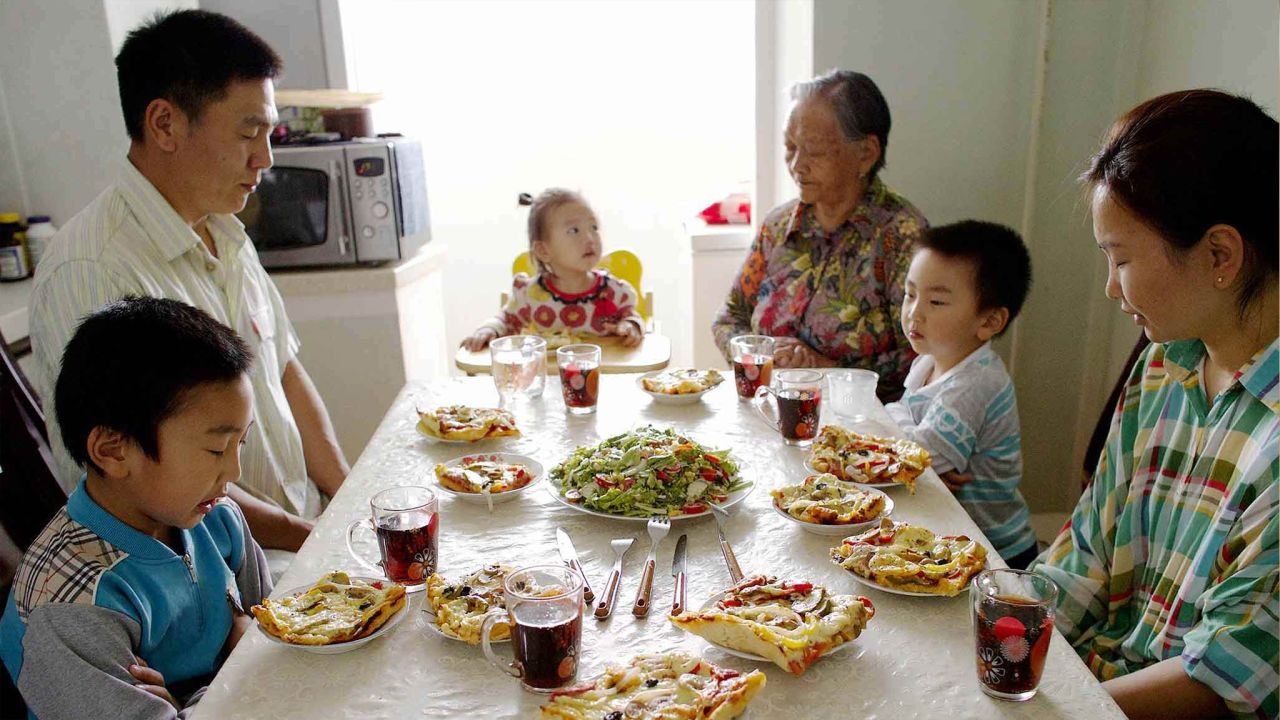 A family pray together at their kitchen table before eating dinner