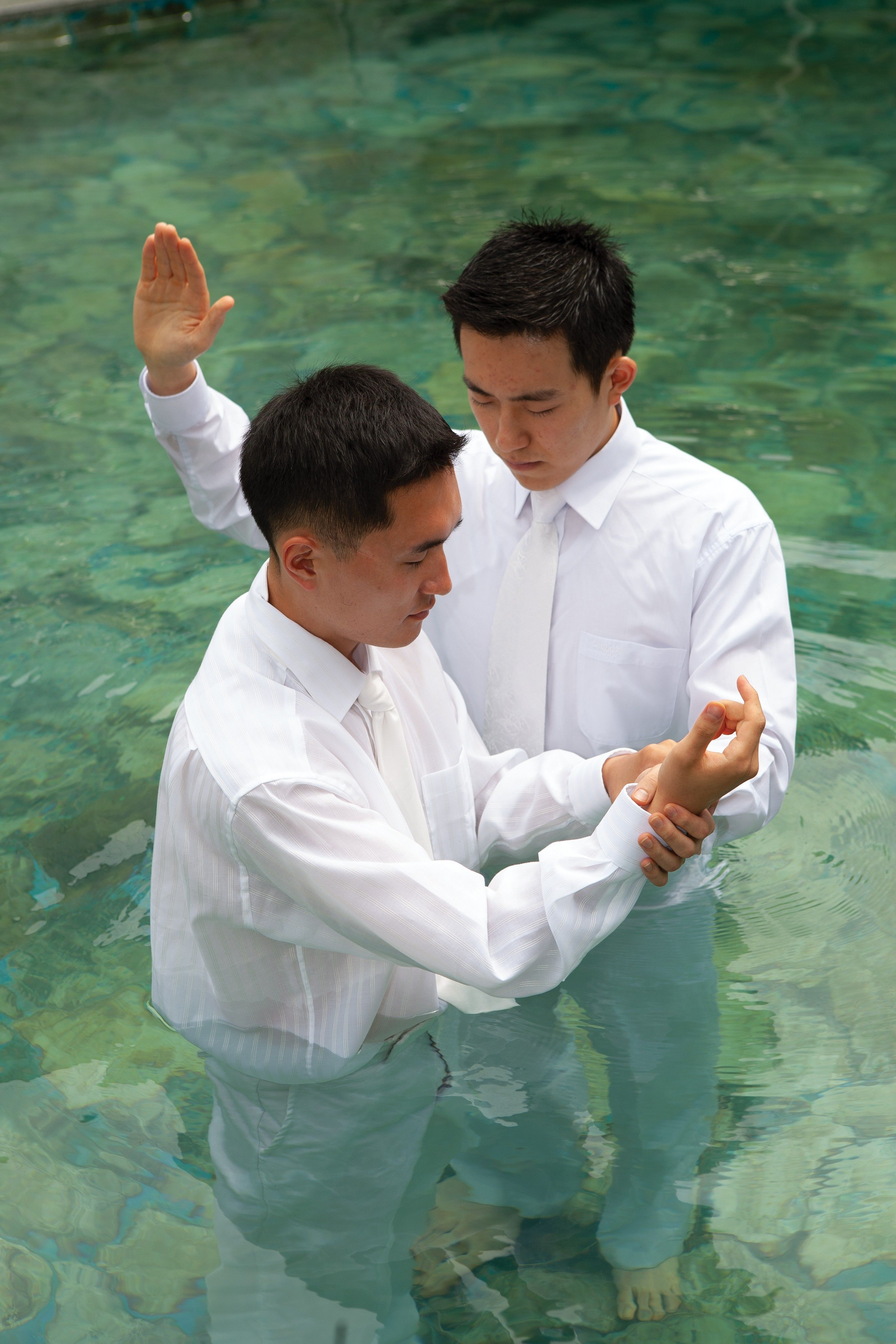 A young man in white clothing being baptized by another young man in an outdoor pool of clean water with rocks seen at the bottom.