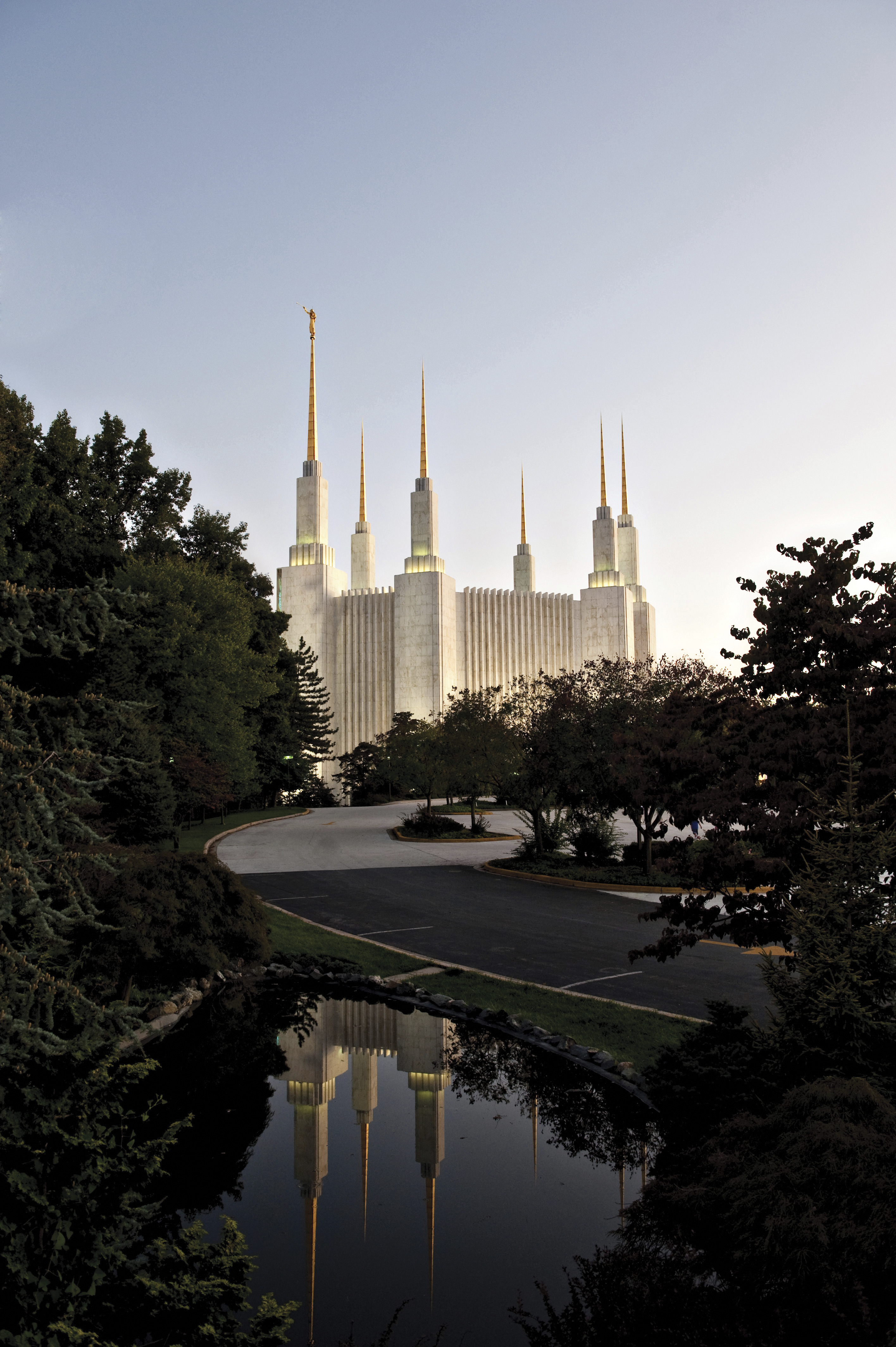 The Washington D.C. Temple during sunset, with the road and pond.