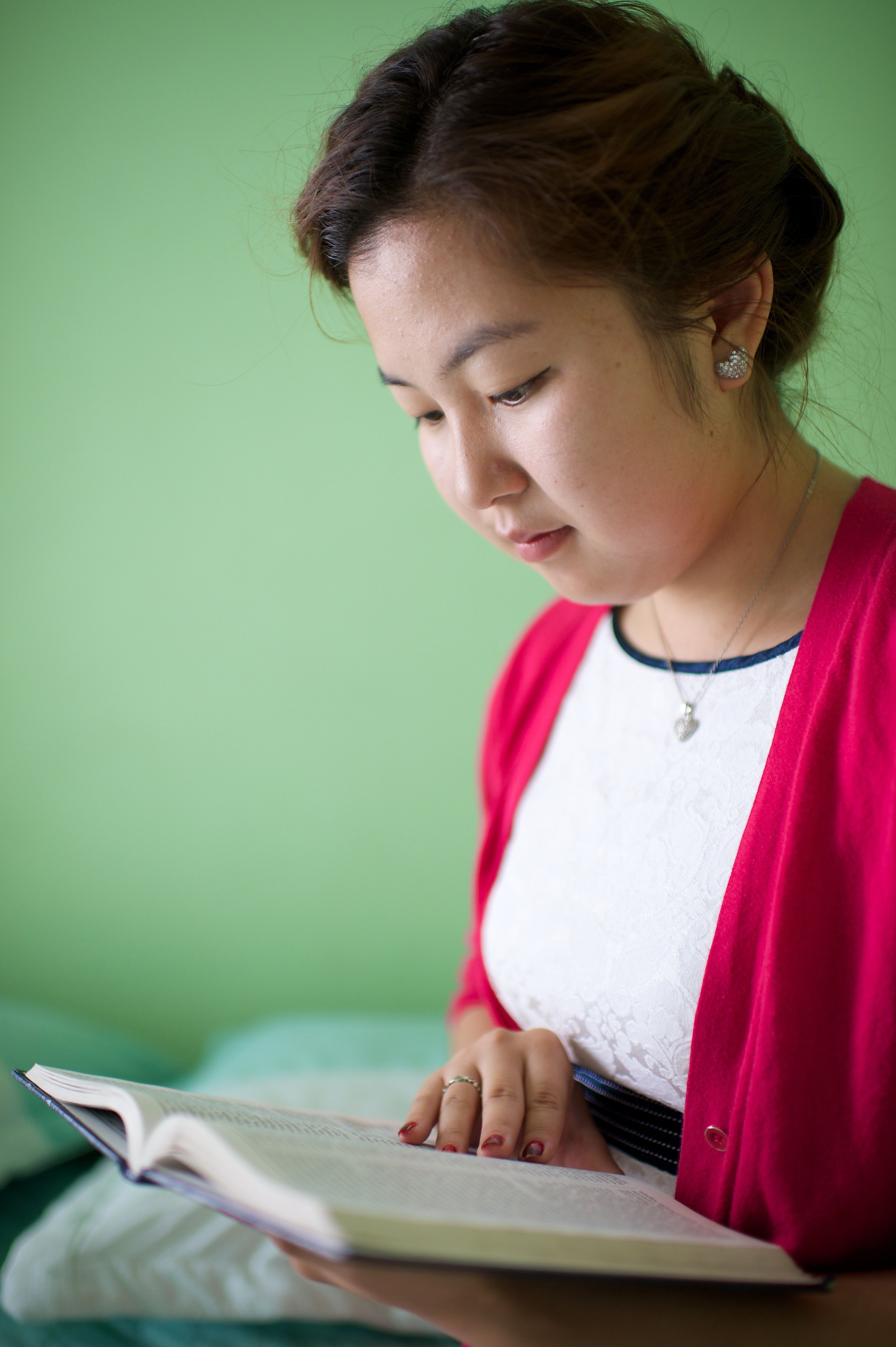 A young woman sits on her bed and reads from her scriptures.