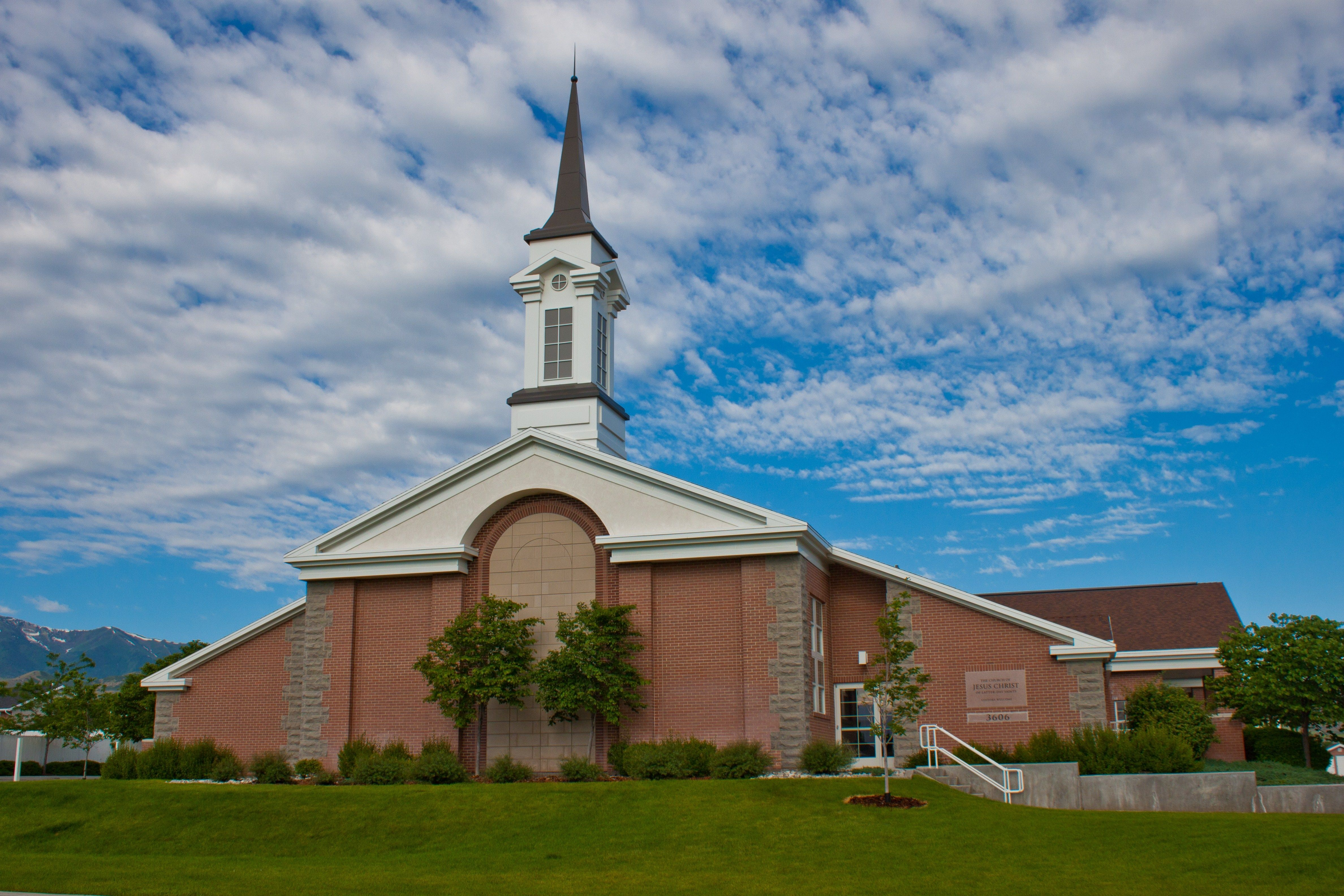 A large red-brick chapel with a blue sky and clouds above.