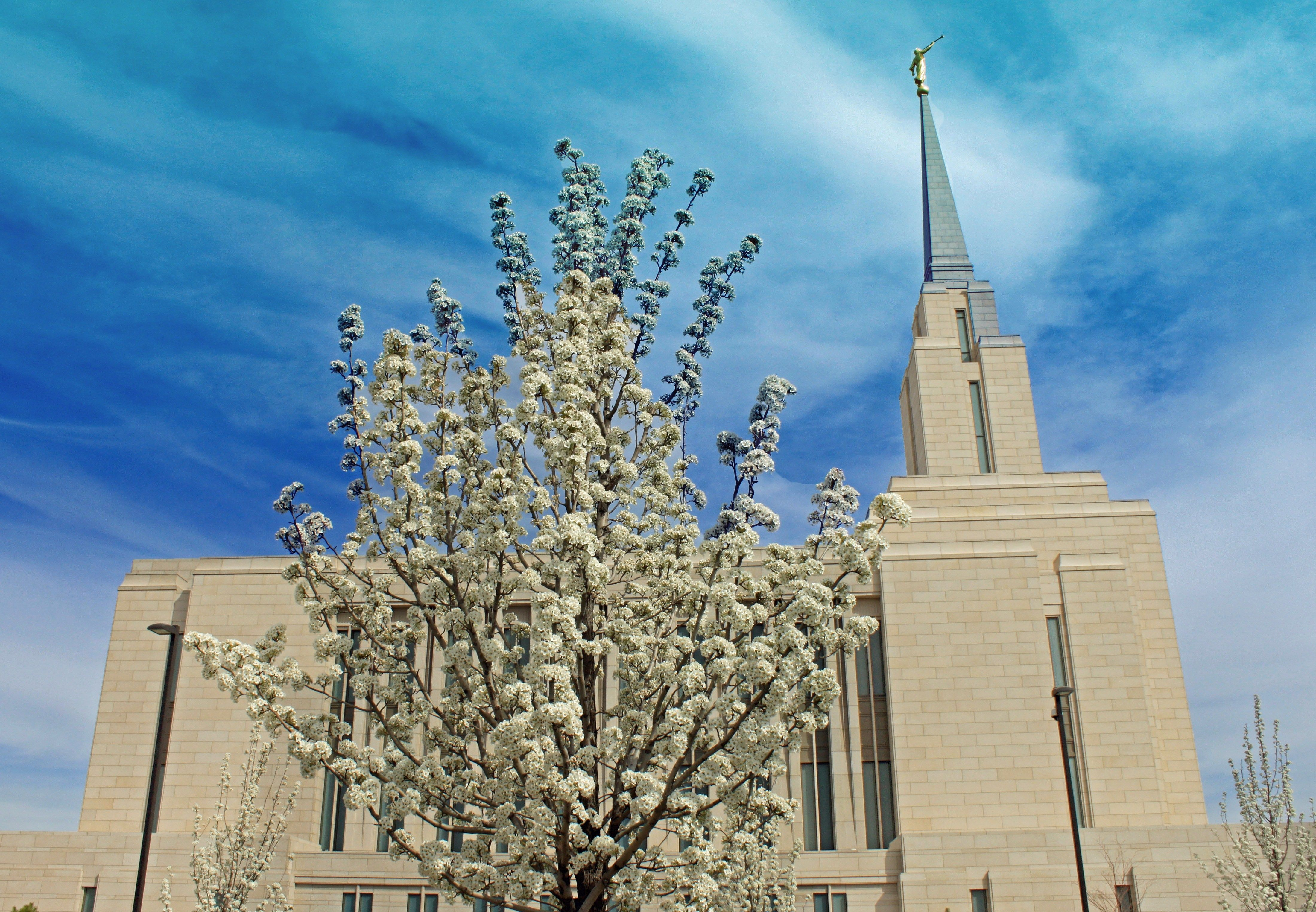 The Oquirrh Mountain Utah Temple side view, including the exterior of the temple, the spire, and scenery.