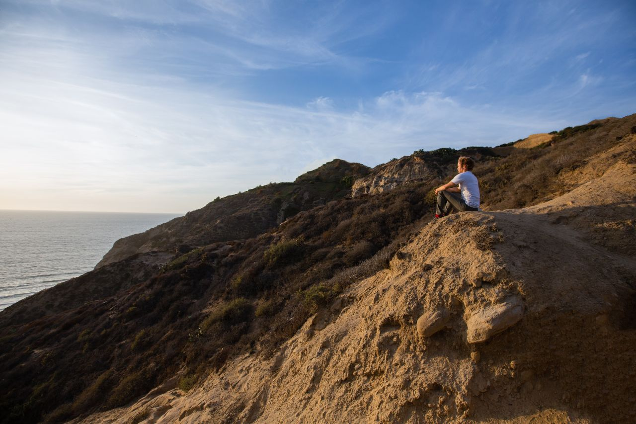 A woman sits on a cliff overlooking the sea contemplates forgiveness and repentance