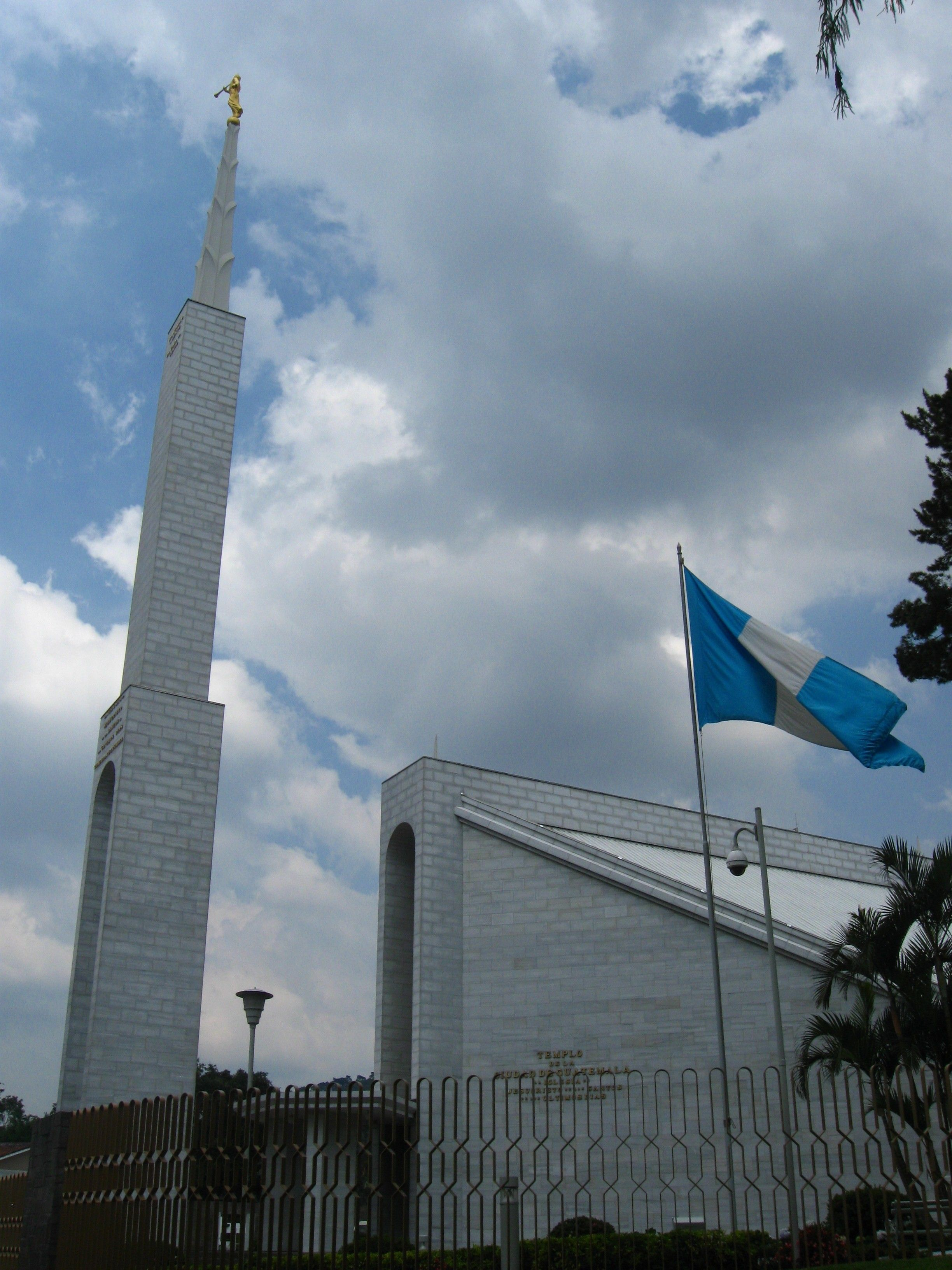 The Guatemala City Guatemala Temple side view, including the spire, flag, and gates.