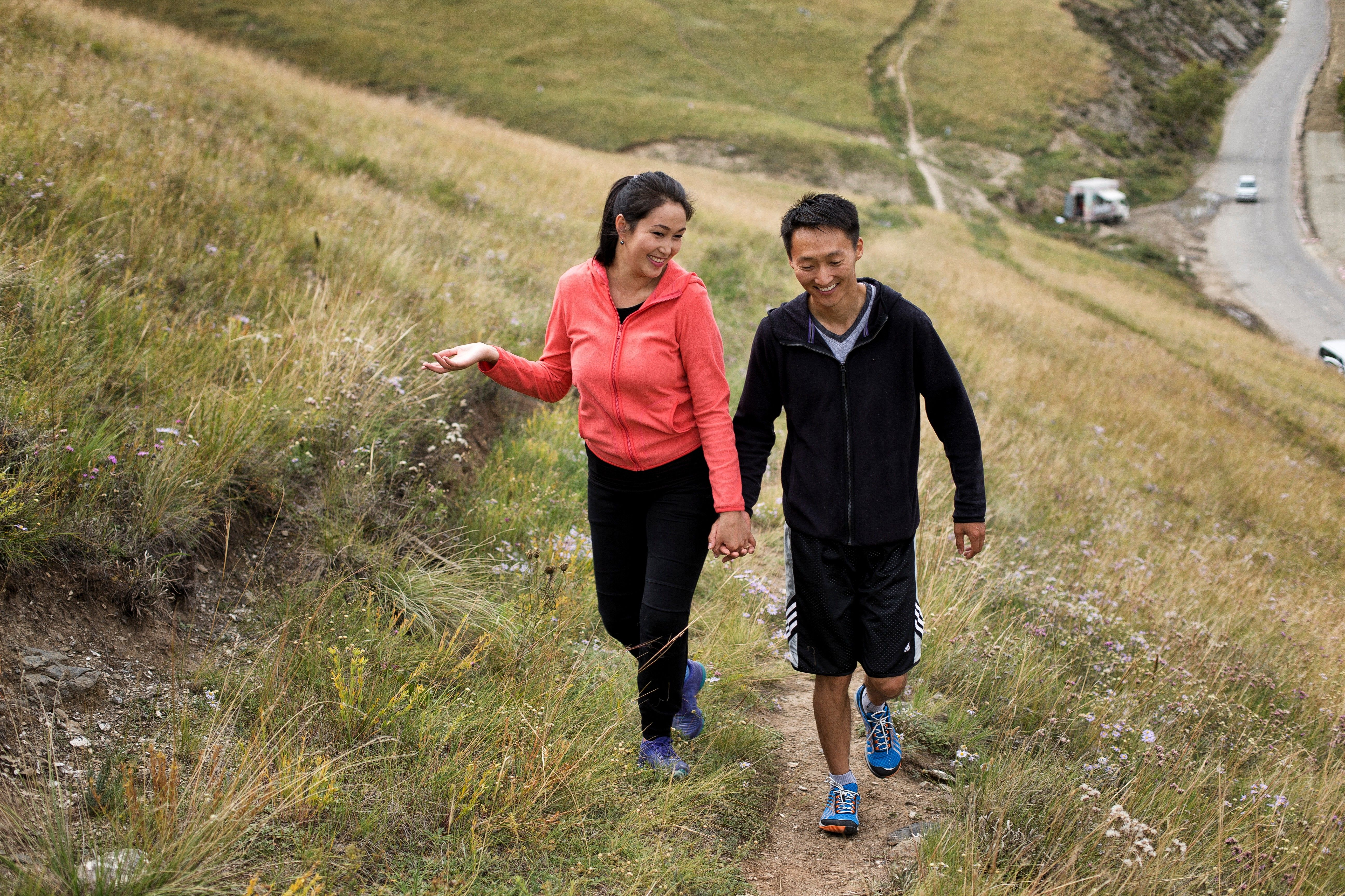 A couple from Mongolia holding hands while hiking up a hill together.