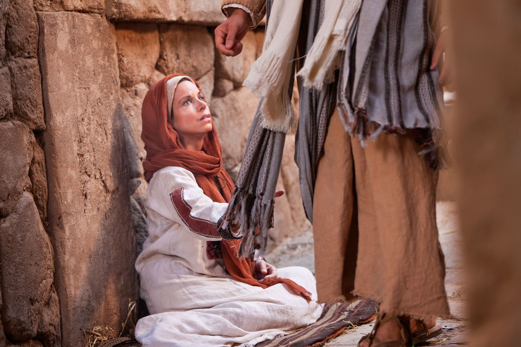 A woman with an issue of blood touches the clothes of Jesus.