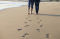 Couple Walking Across Beach Shoreline Leaving Footprints