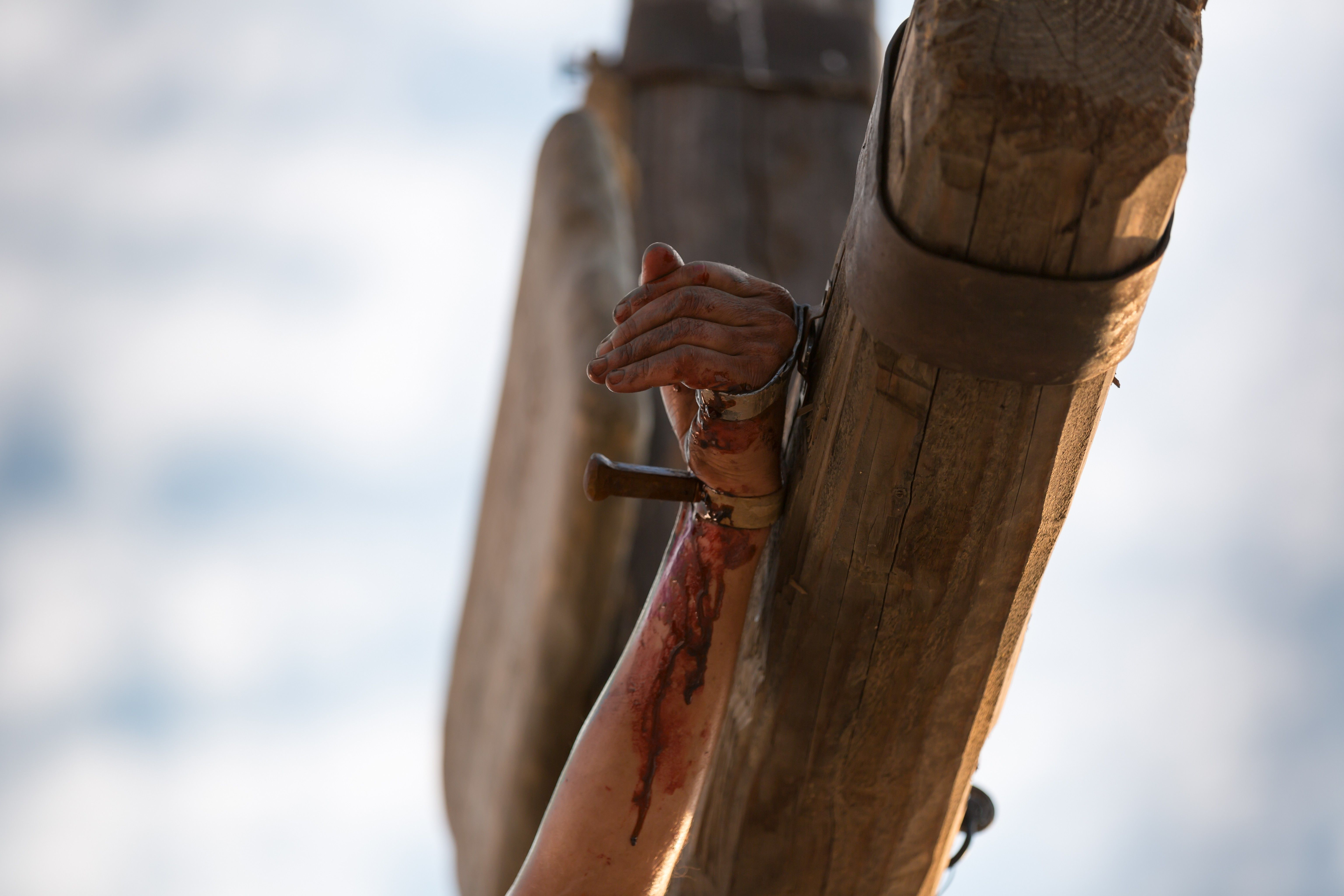 Christ's arm on the cross, with nails through His wrist and hand.