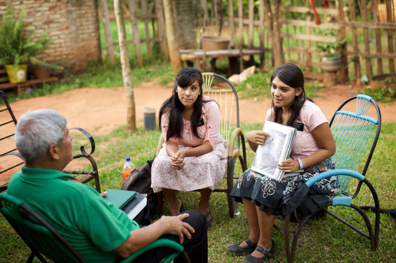 Dos misioneras le enseñan a un hombre mayor sobre el Plan de Dios