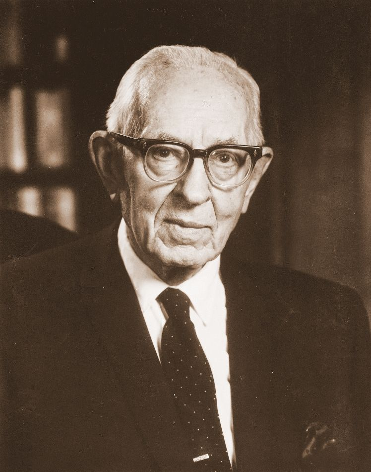 A formal portrait of the prophet Joseph Fielding Smith in a dark suit, a tie with white specks, and glasses.
