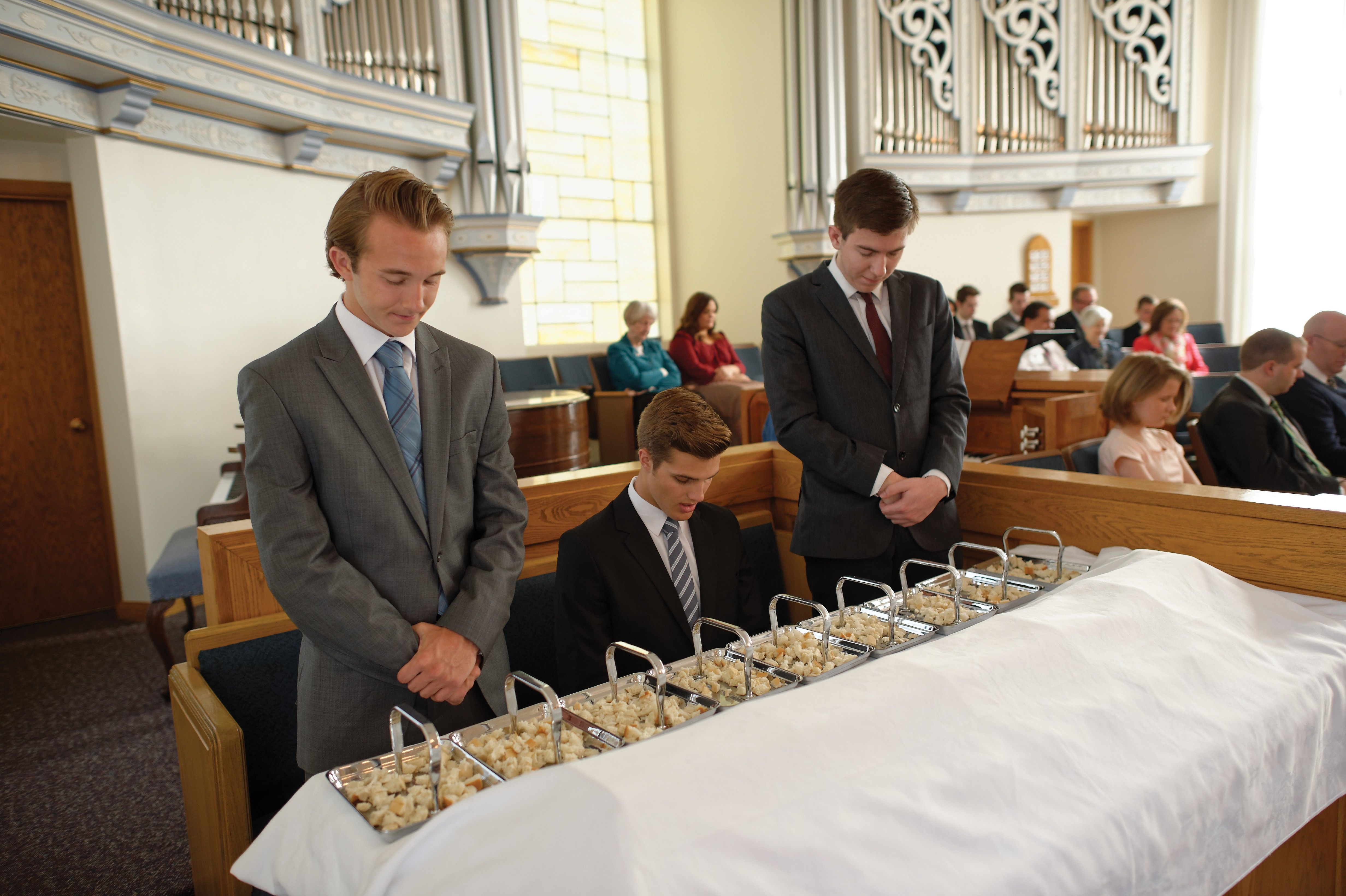 Three young men blessing the sacrament bread for the congregation.