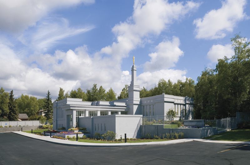 A view of the whole Anchorage Alaska Temple from one of the corners, including some of the parking lot in the foreground.