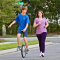 brother on unicycle and sister running