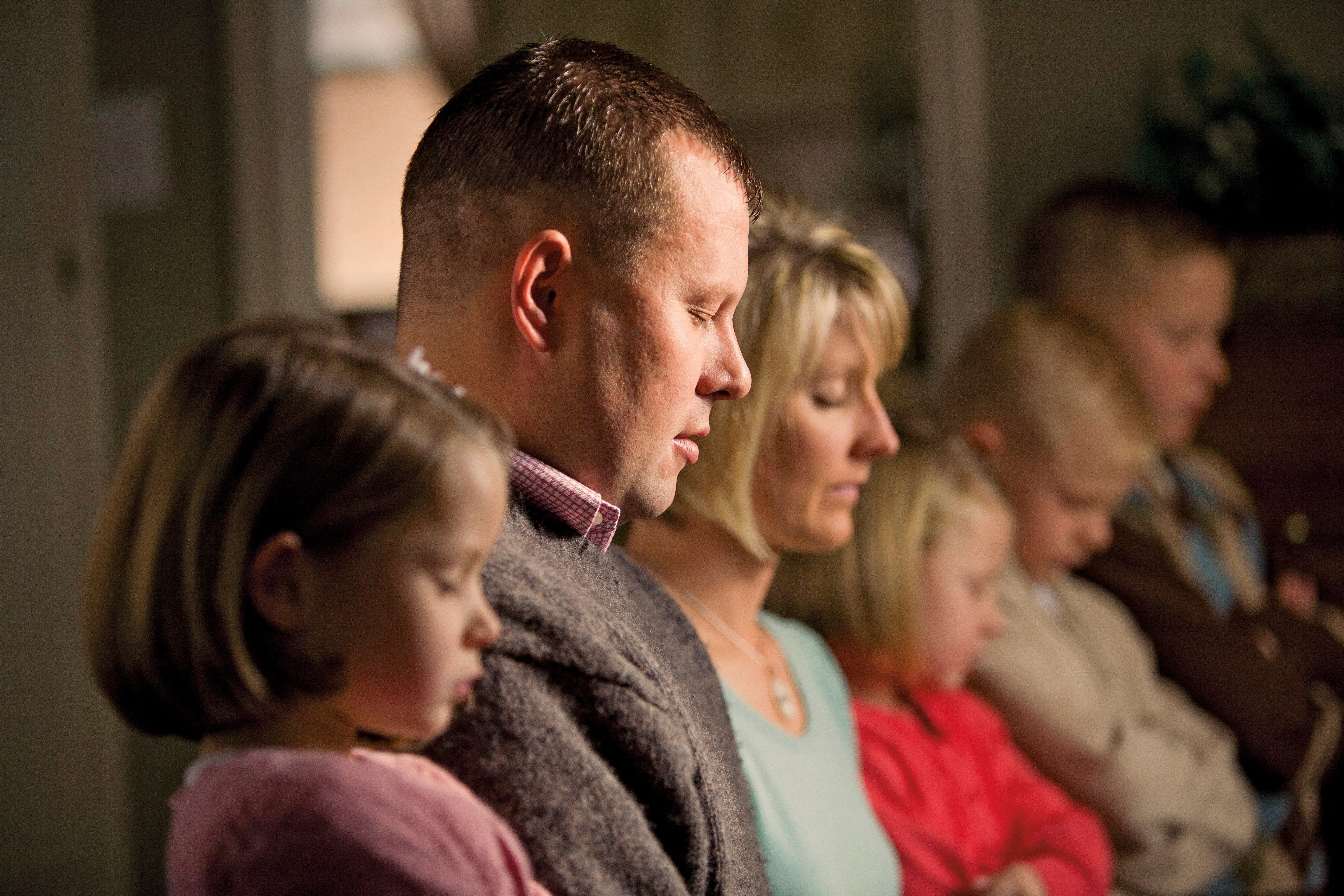 A father prays with his family.