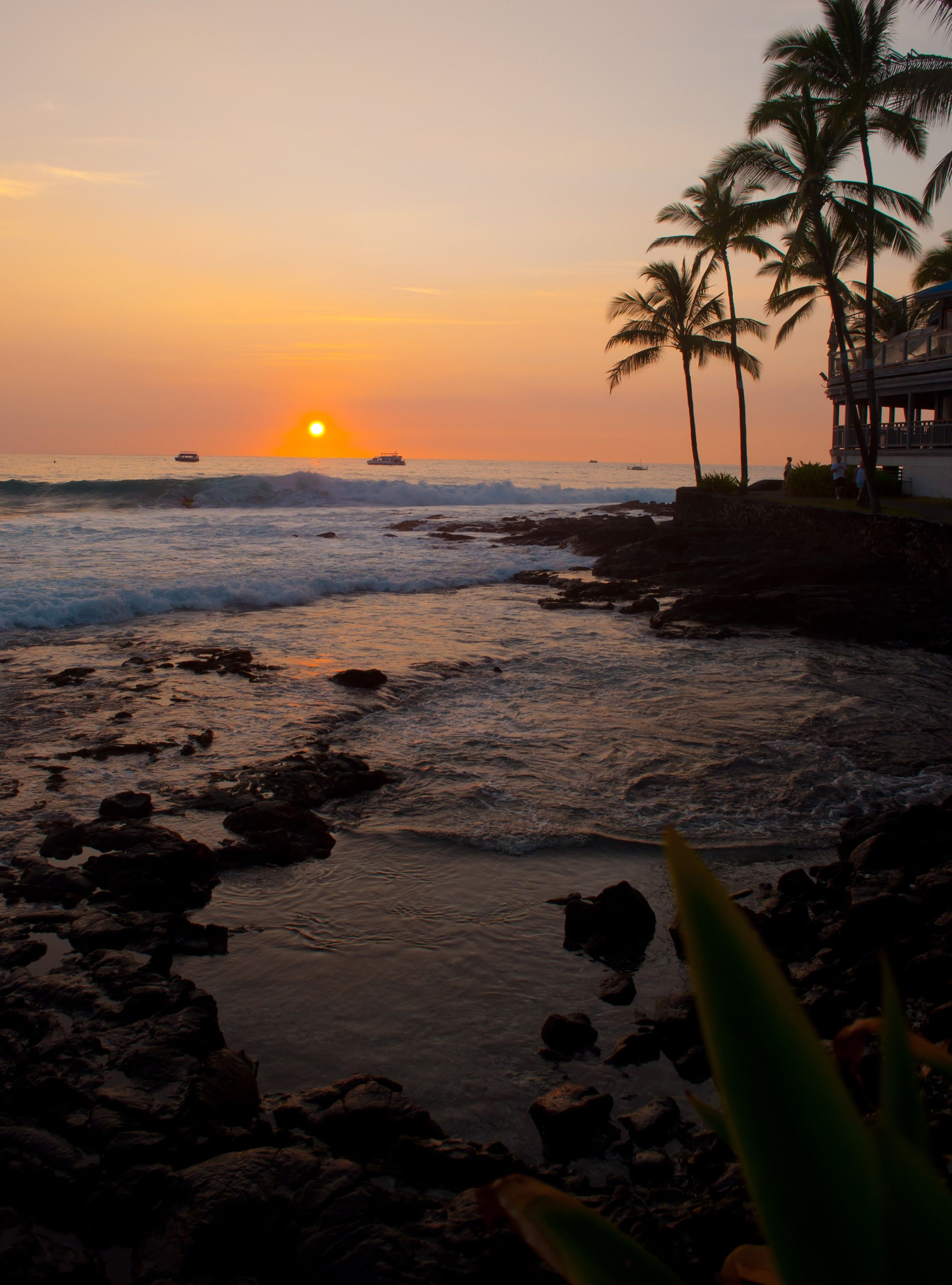The sun sets over the ocean, with a view of the shore and palm trees.