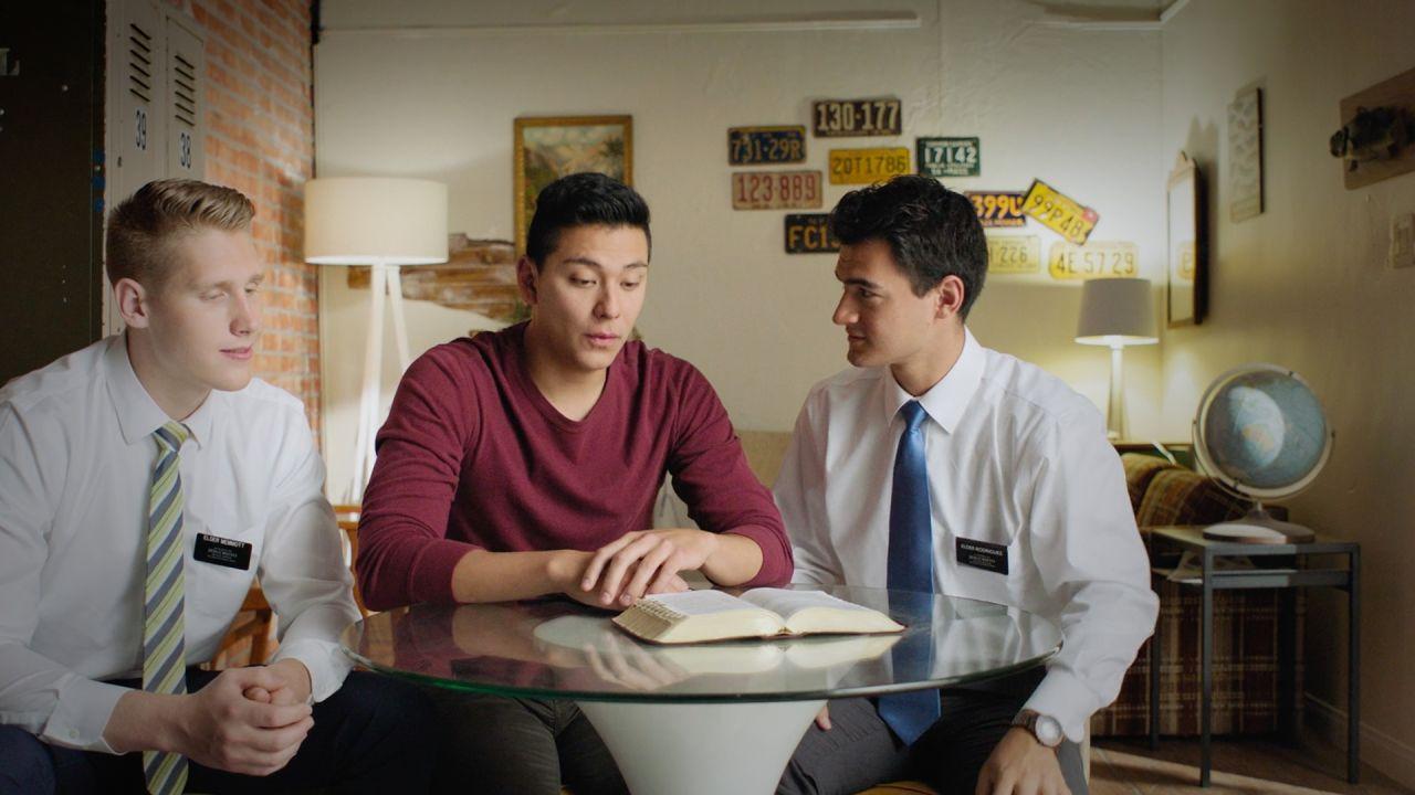 Misioneros Santos de los Últimos Días enseñando con el Libro de Mormón