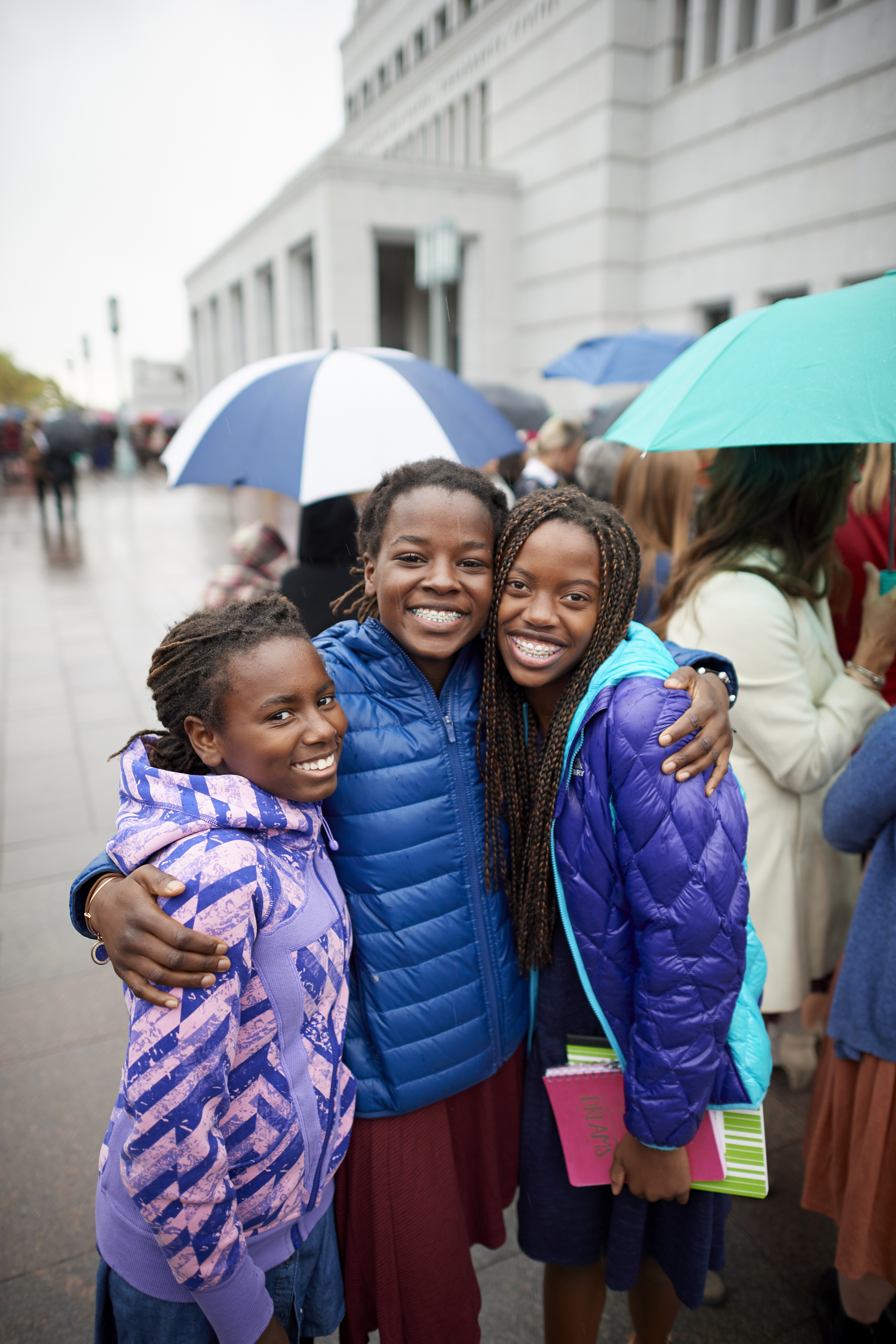 Three young women attending the general women's session of general conference together.