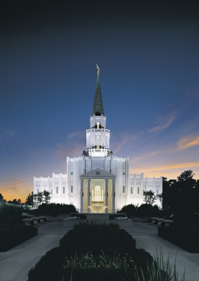 The front of the Houston Texas Temple from afar at night, with all of the lights on inside and outside and a dark blue sky beyond.