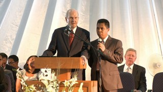 Elder Nelson speaks from a pulpit with a translator next to him