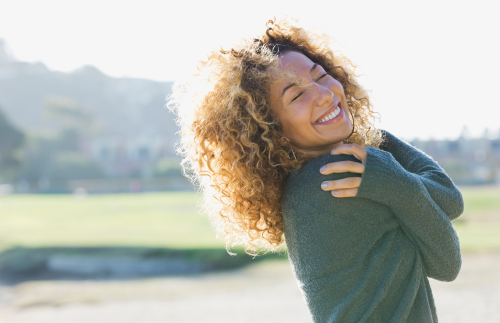 Smiling woman with eyes closed outdoors
