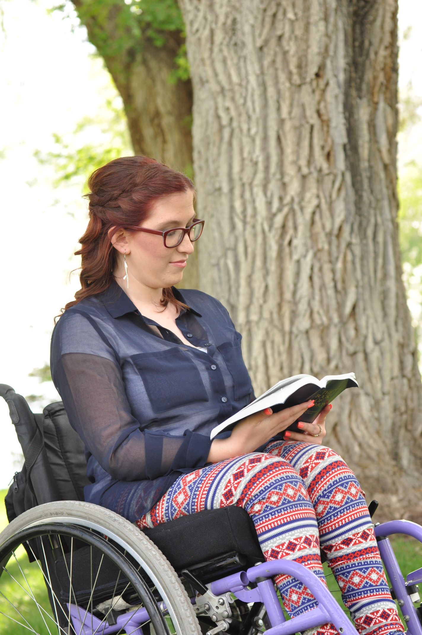 A young woman in a wheelchair reading the Book of Mormon.