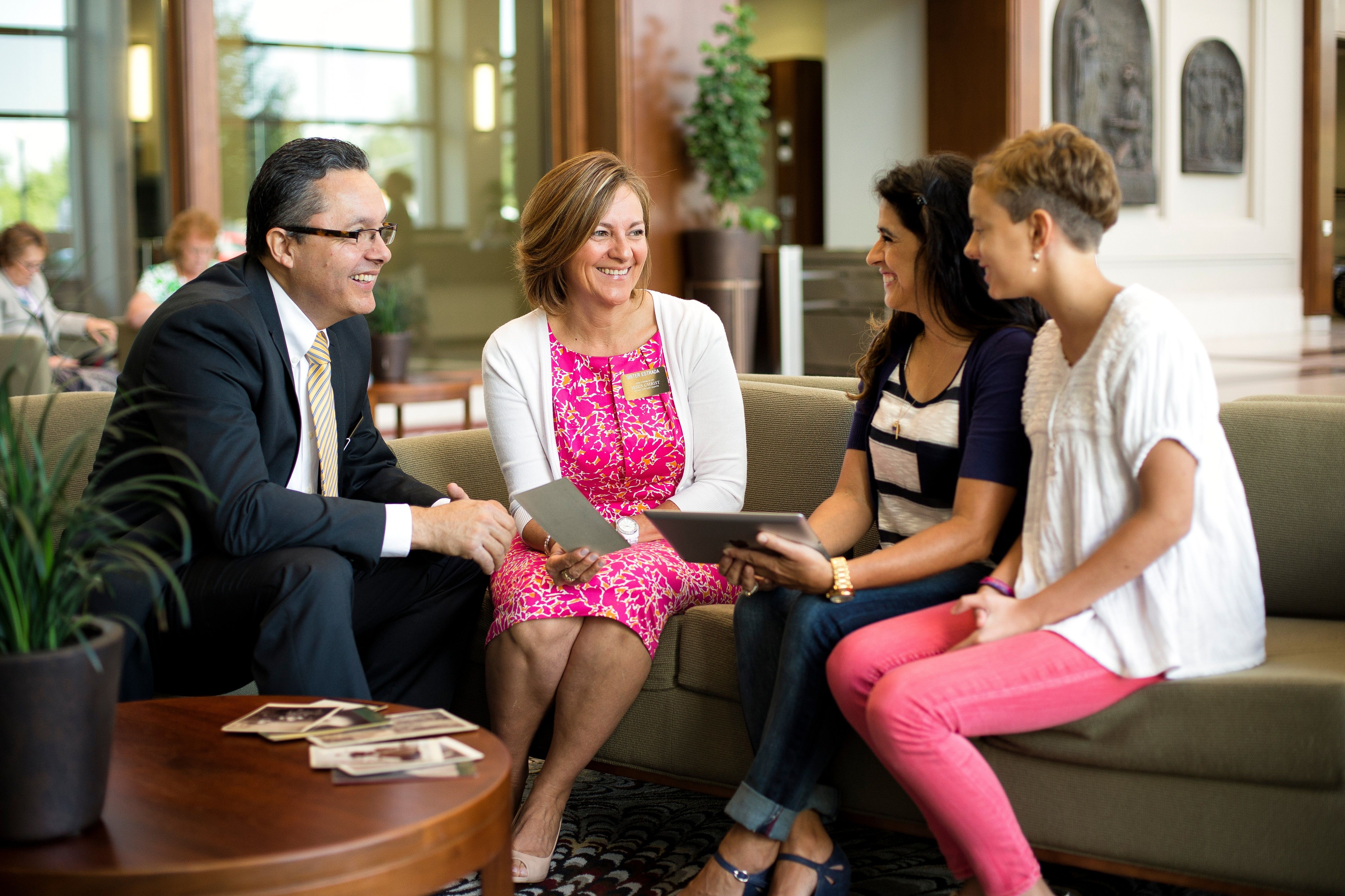 A senior missionary couple teaching family history to a mother and daughter.