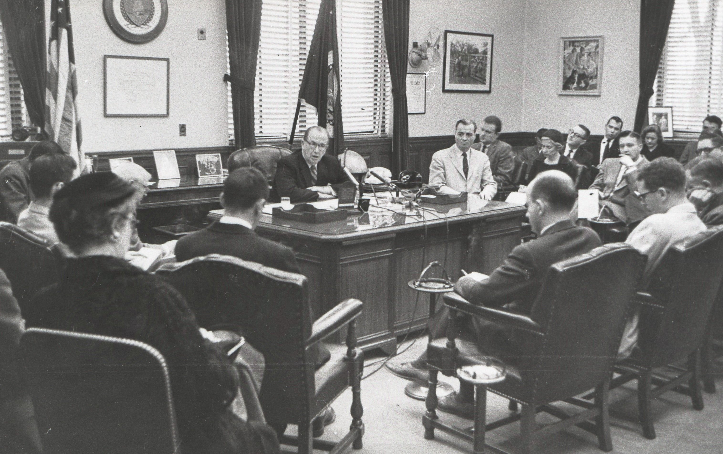 President Benson sitting behind a desk and speaking to a group of men and women.