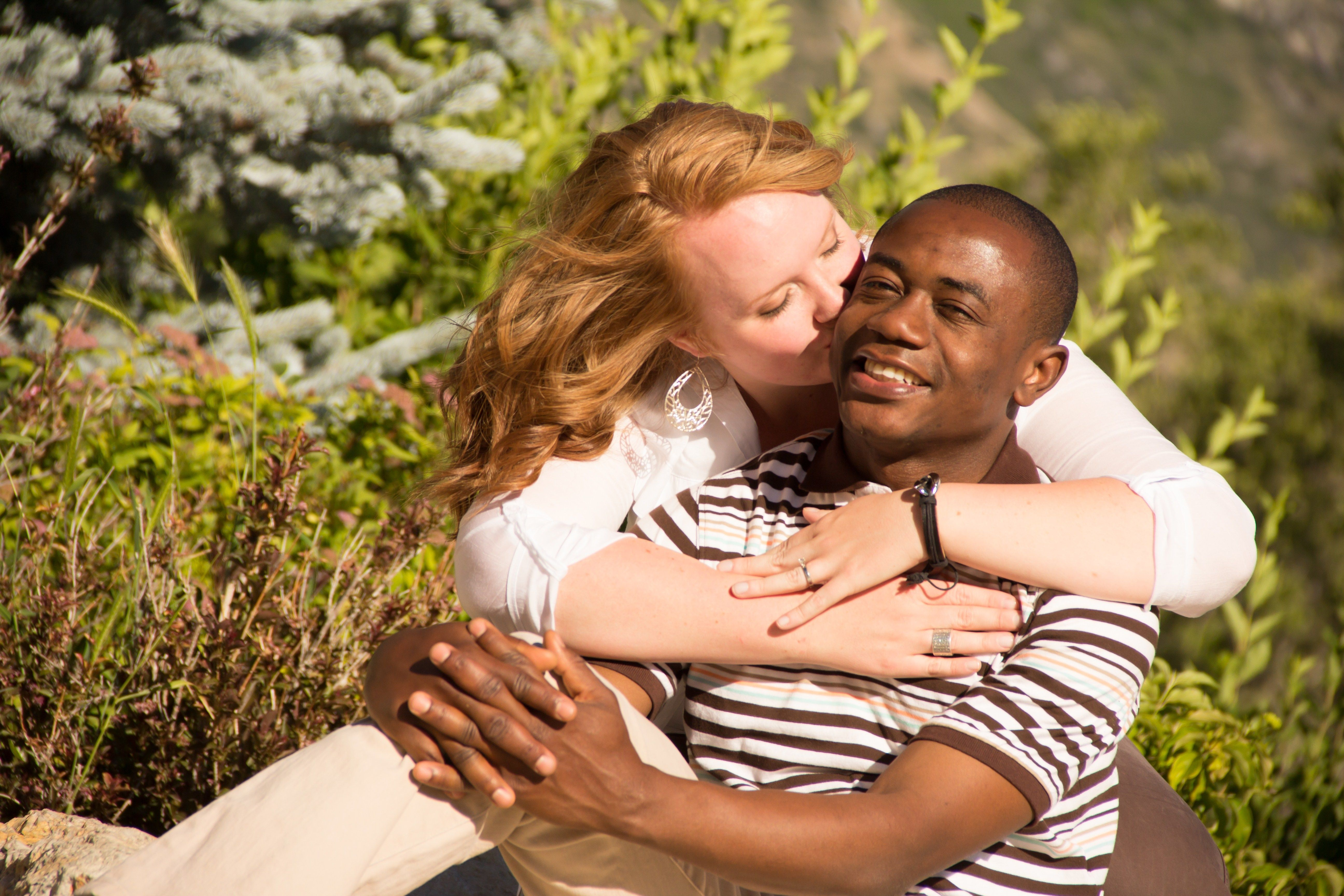 A woman kisses a man's cheek in an engagement picture.