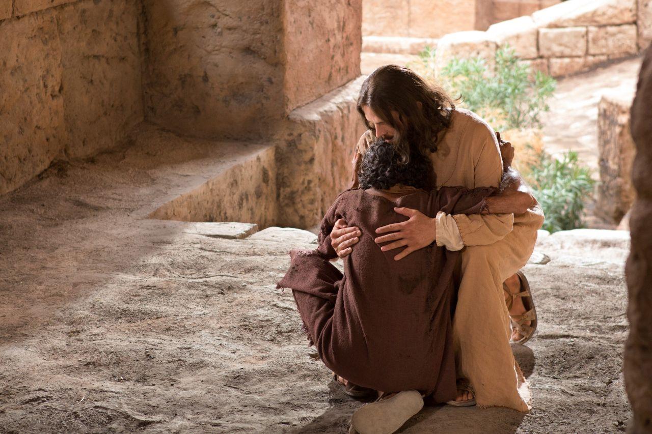 Un hombre y Jesús se funden en un abrazo mientras caen al suelo