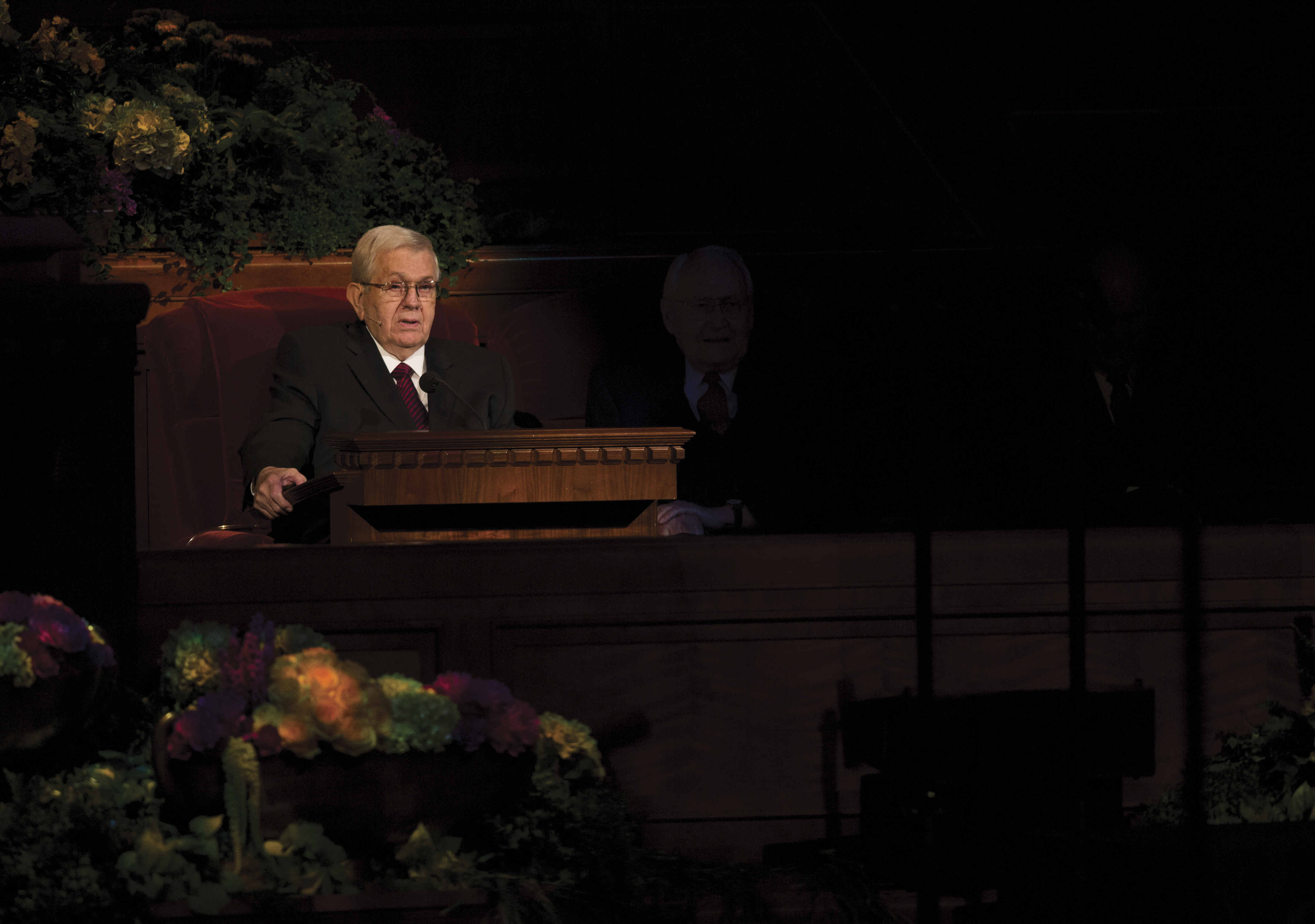 Boyd K. Packer sitting and speaking to the congregation at general conference.