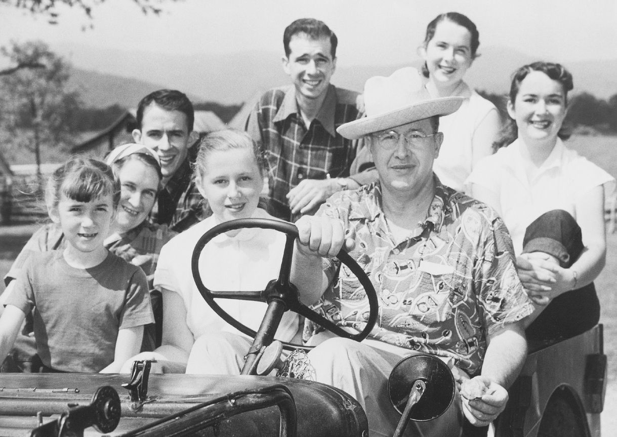 President Benson sitting behind the steering wheel of a car with his children.