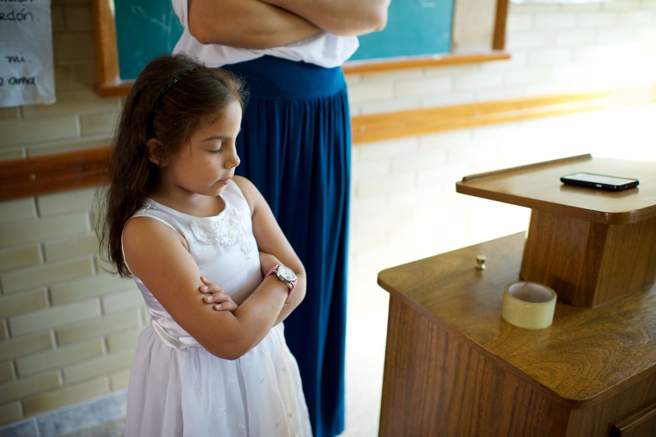 A young girl folds her arms in prayer during a primary meeting