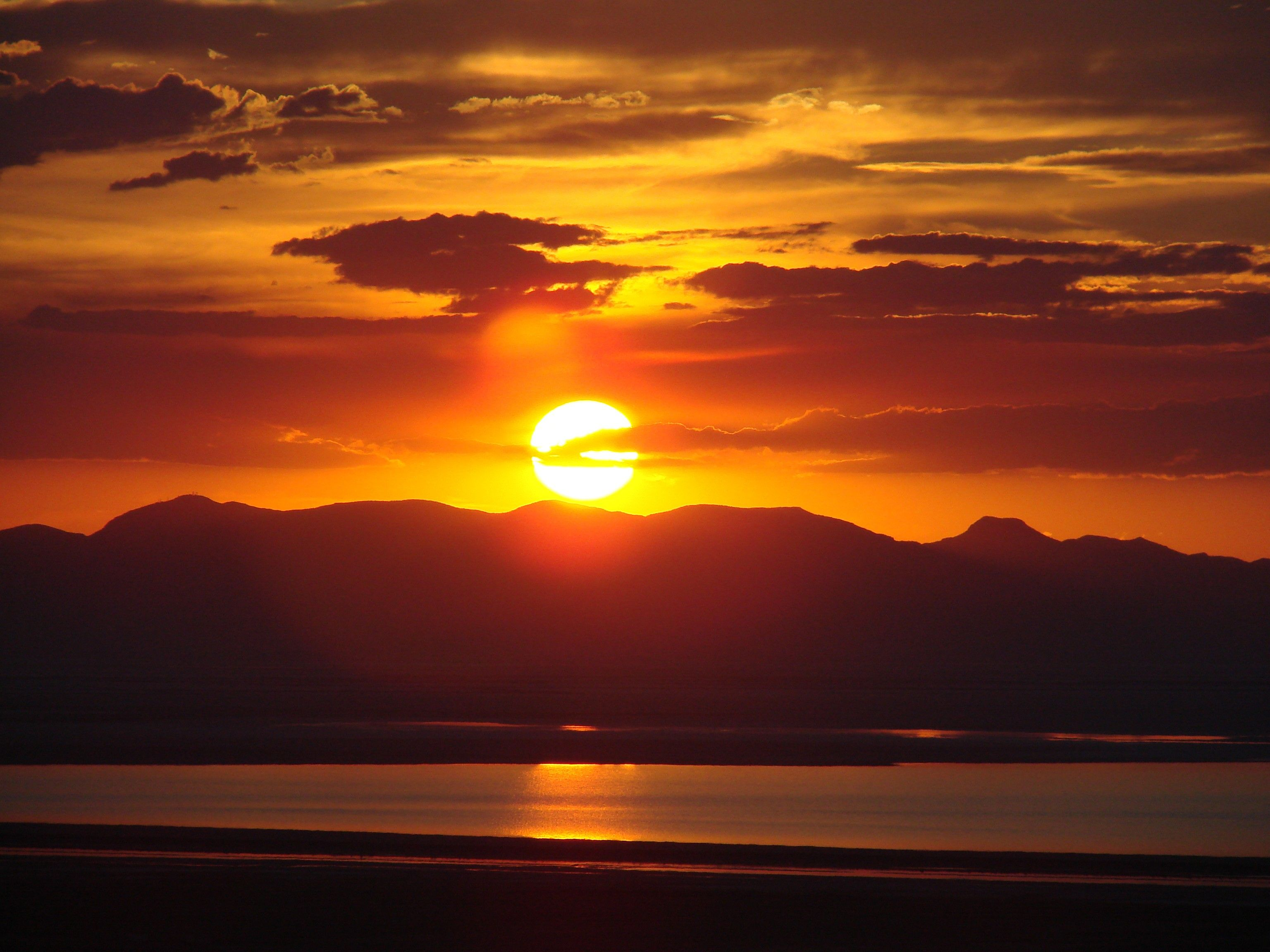 The sun sets behind mountains and the Great Salt Lake.
