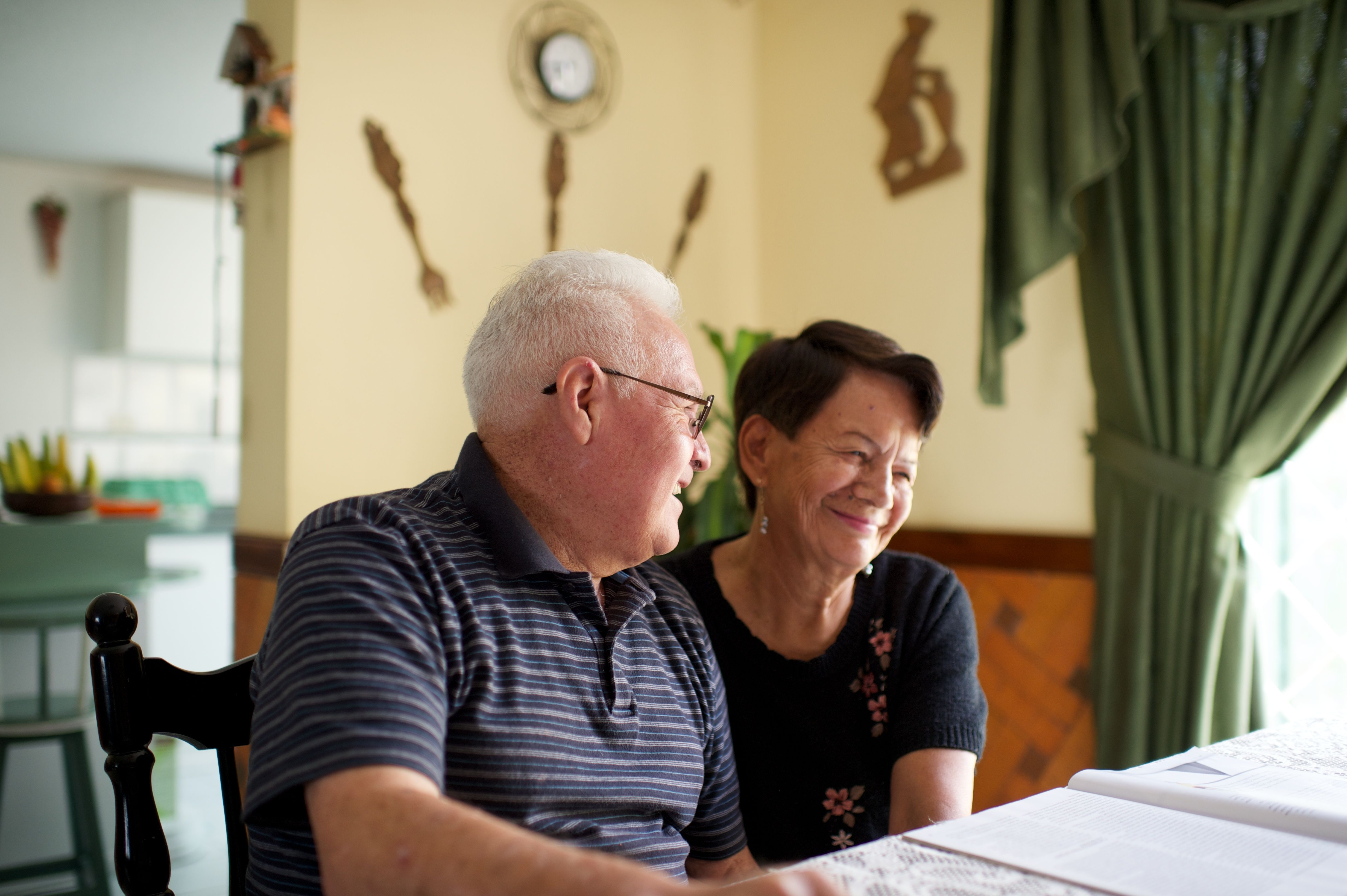 An elderly couple sits in chairs at their house and laughs together.