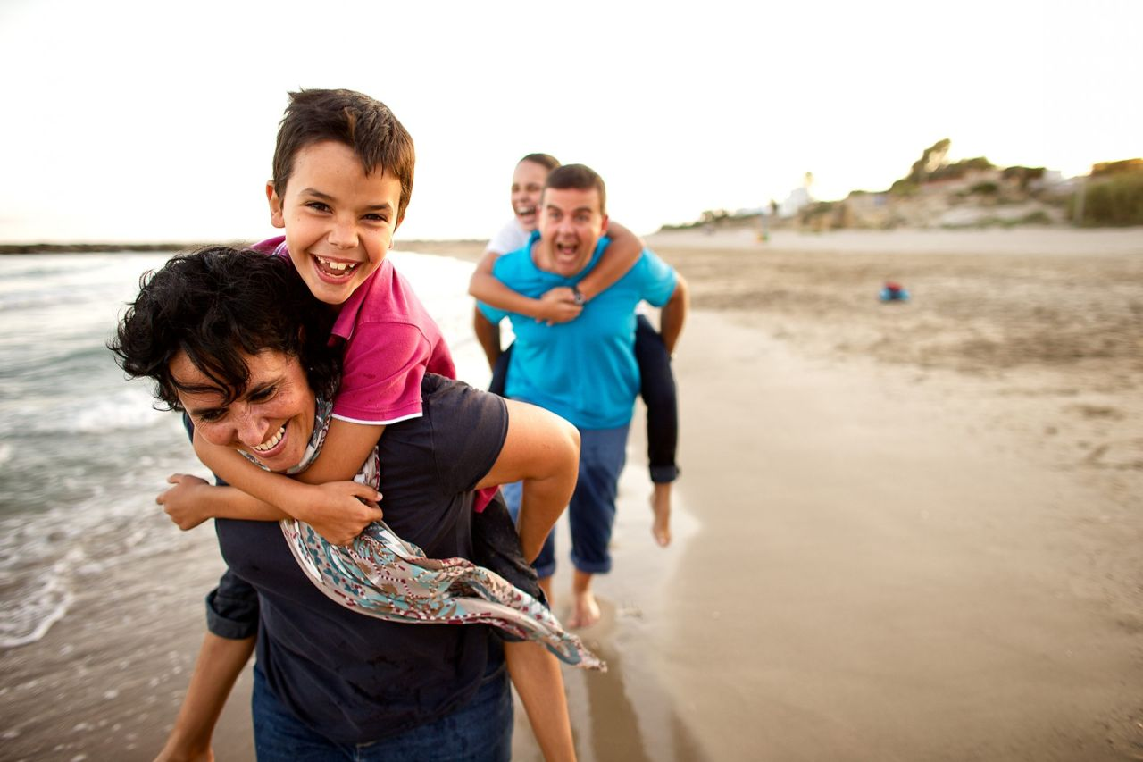 A family runs around playing on a beach enjoying each others company