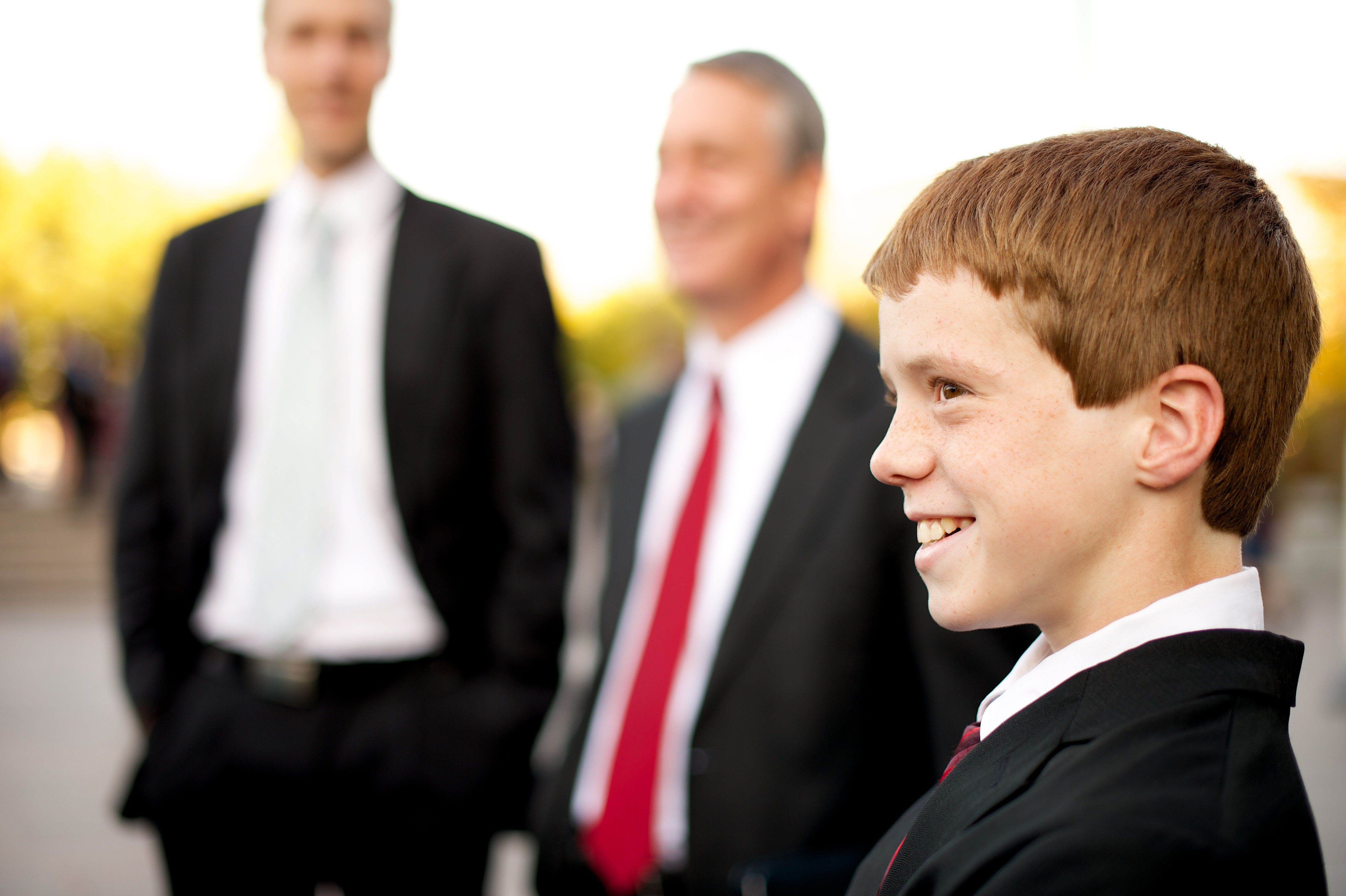 A young man in a suit stands outside of the Conference Center and smiles.