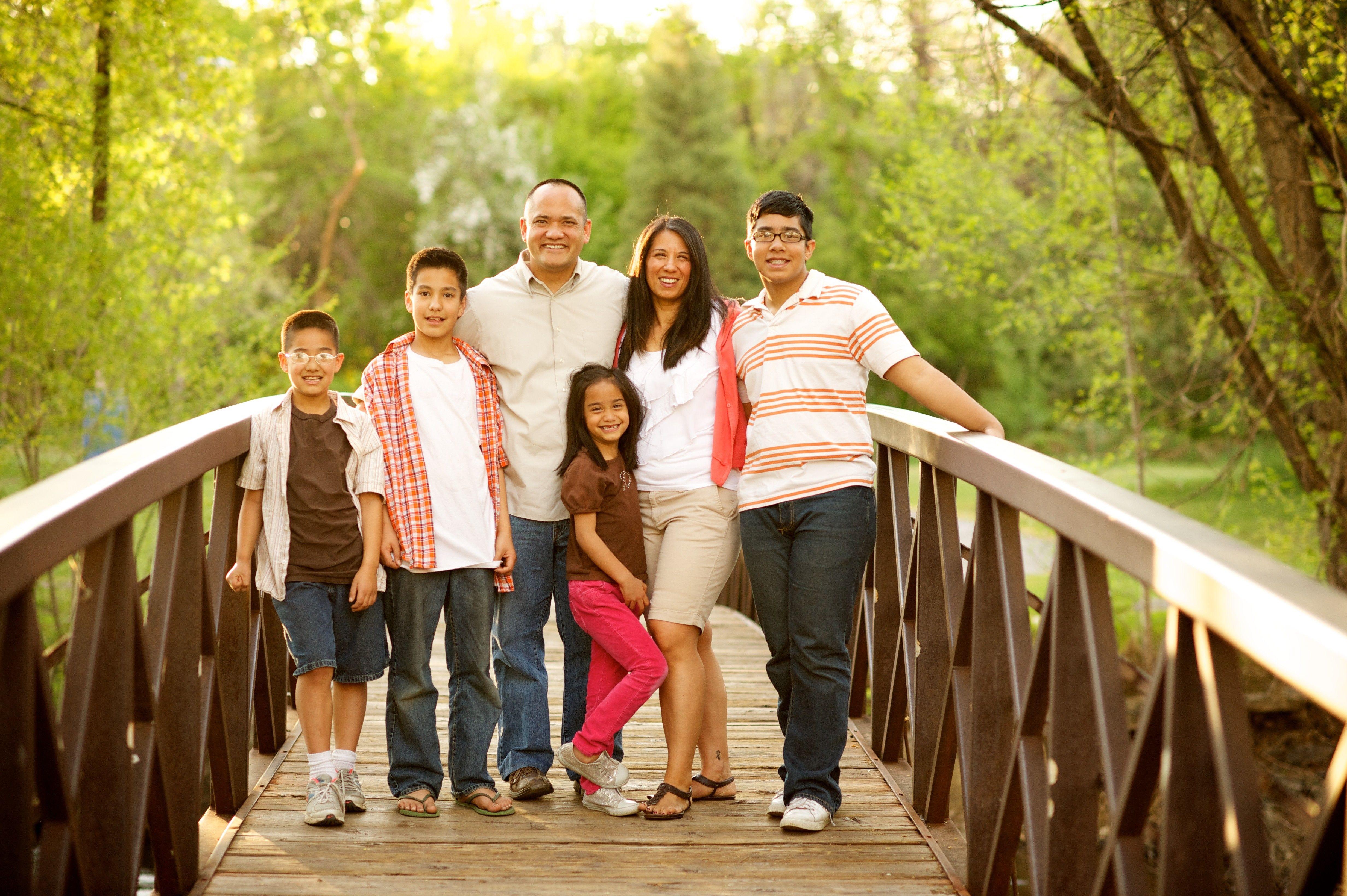 A family has their portrait taken on a bridge.