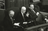 President Benson sitting in a large armchair between his counselors, smiling and waving to the audience in the Tabernacle.