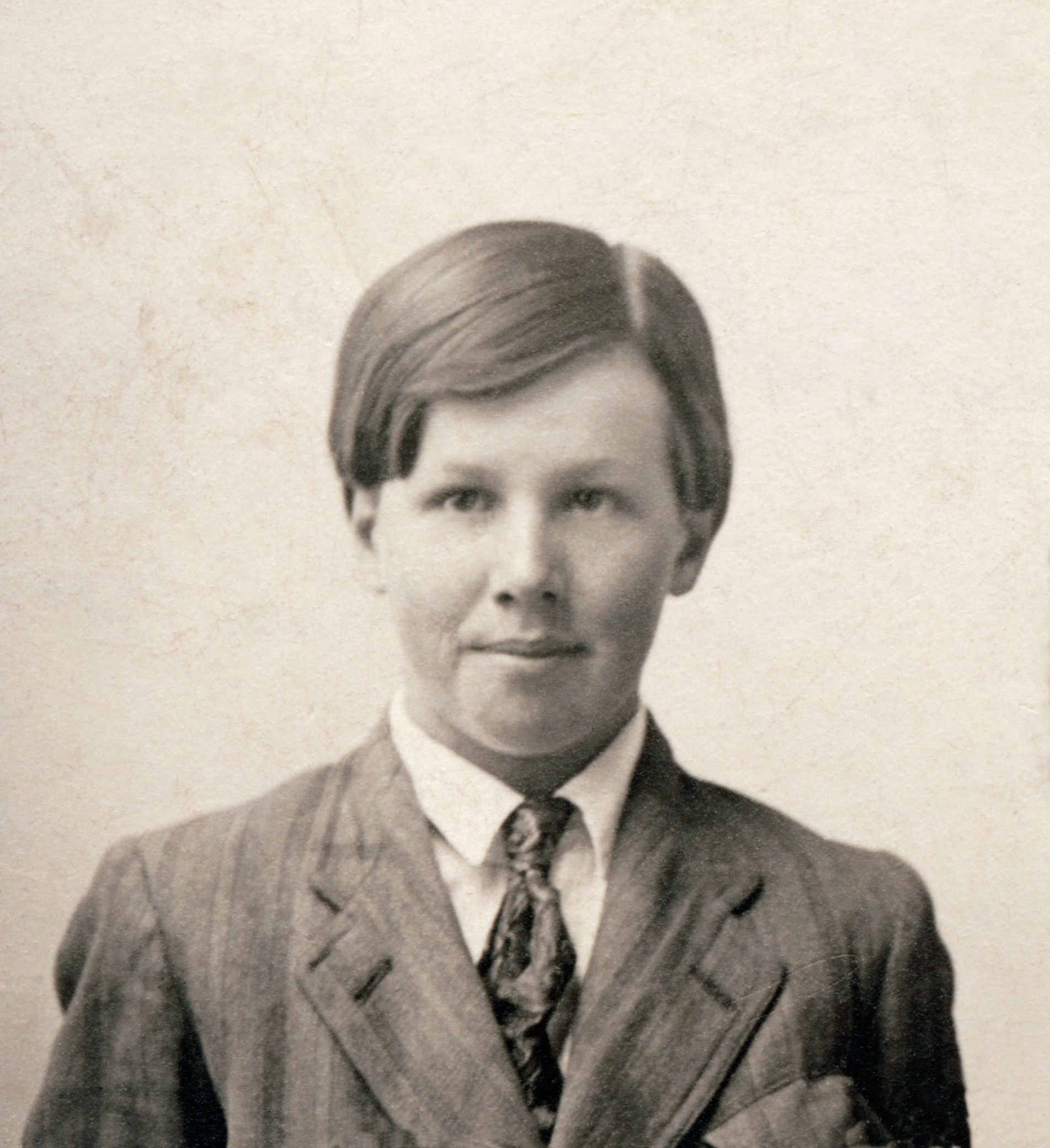 President Benson as a young man with his hair parted, wearing a suit and tie.